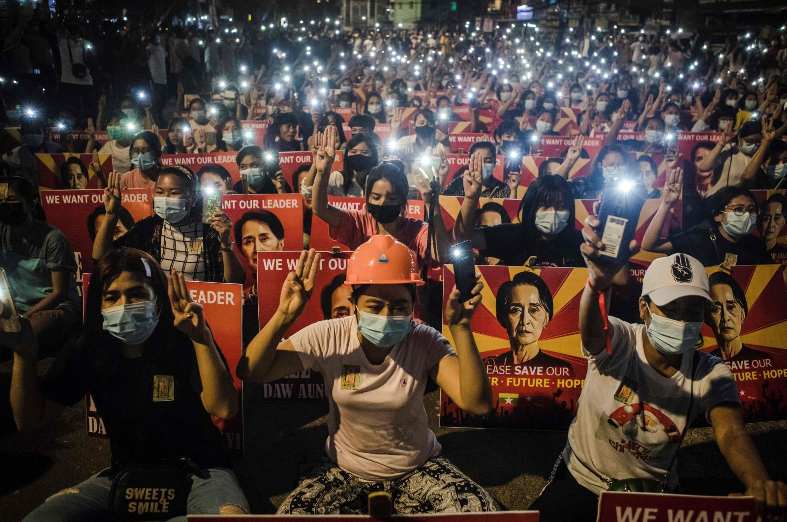 Protesters hold up the three finger salute and placards with the image of detained Myanmar civilian leader Aung San Suu Kyi while using their mobile torches during a demonstration against the military coup in Yangon, Myanmar, March 12, 2021. (AFP Photo)