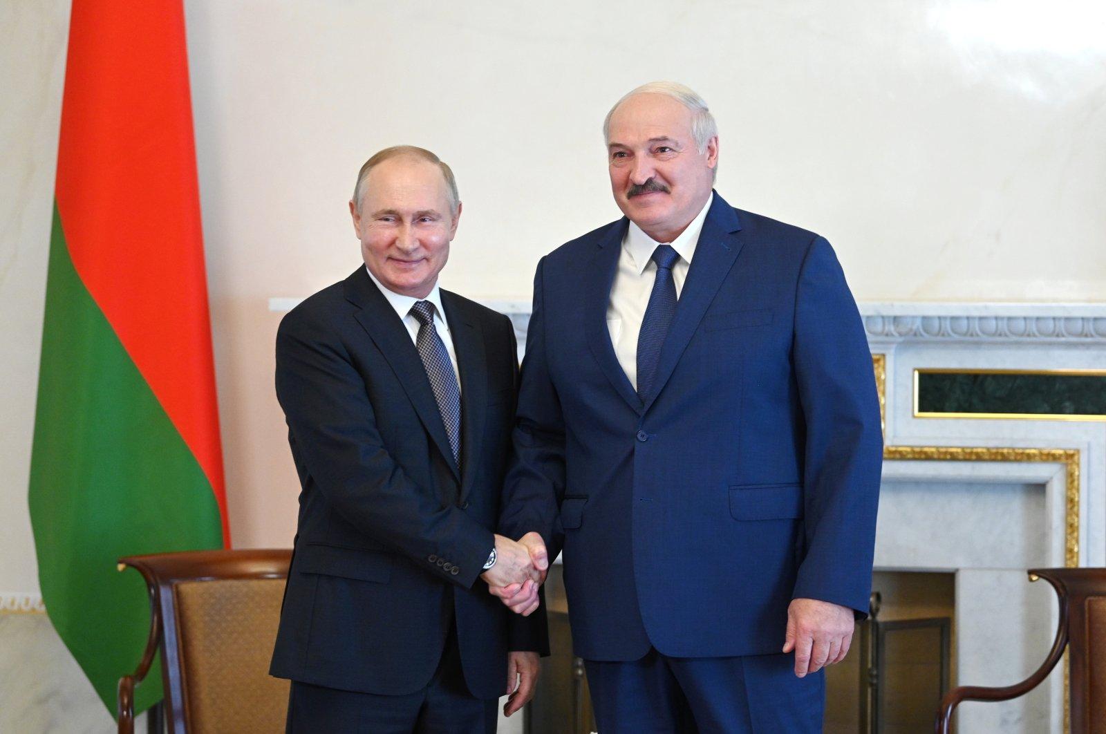 Russian President Vladimir Putin (L) shakes hands with Belarusian President Alexander Lukashenko during a meeting in St. Petersburg, Russia, July 13, 2021. (Kremlin via Reuters)