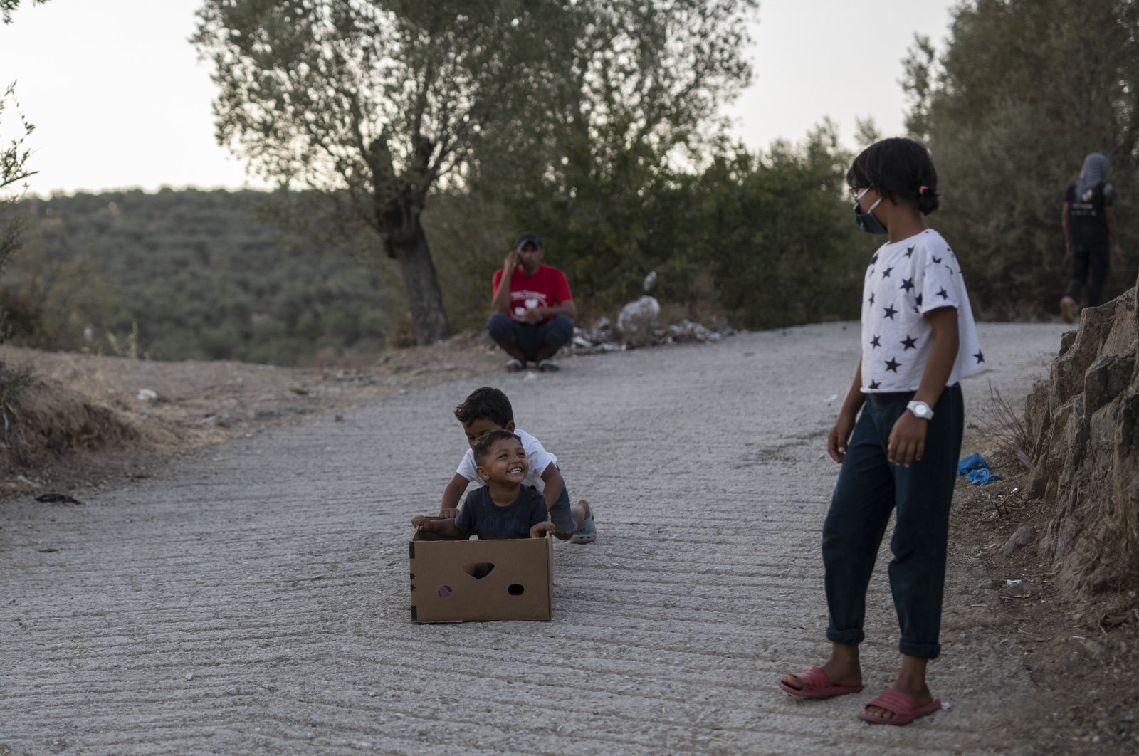 Children play near the burned Moria refugee camp, on the northeastern island of Lesbos, Greece, Sept. 14, 2020. (AP Photo)