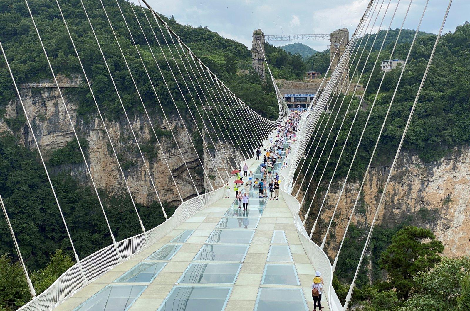 Visitors walk on a 430-meter (1,410-foot) long glass-bottomed bridge over the Zhangjiajie Grand Canyon in Zhangjiajie, Hunan province, China, July 8, 2021. (Reuters Photo)