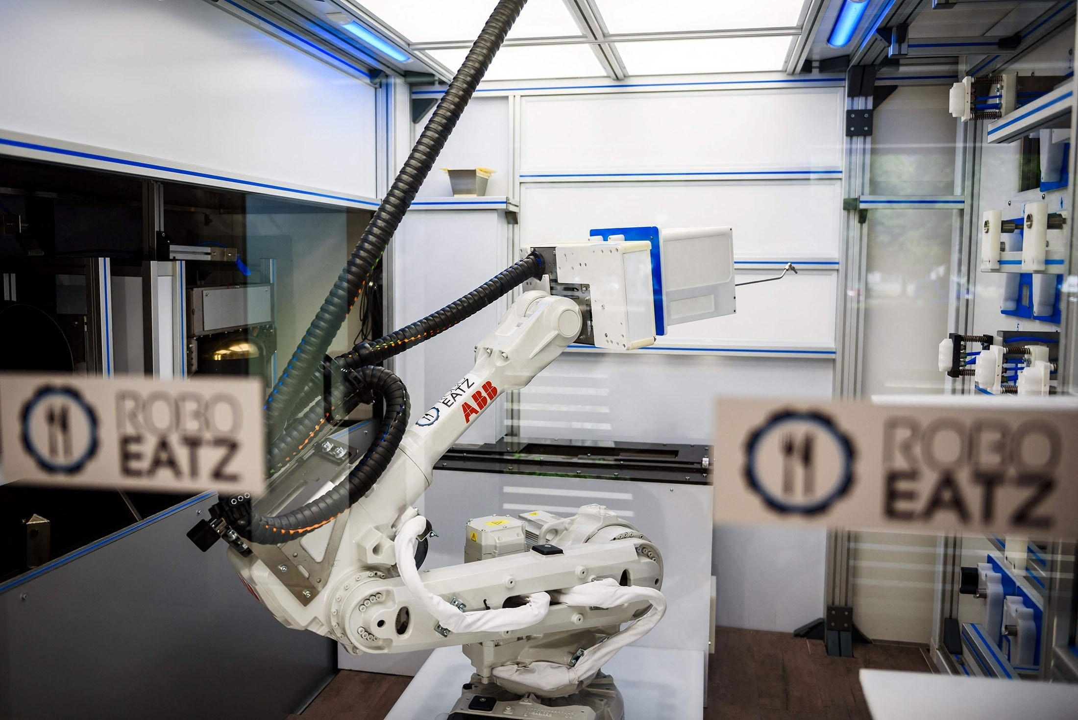 A robot can be seen behind glass as it prepares food at the Roboeatz eatery in Riga, Latvia, May 25, 2021. (AFP Photo)