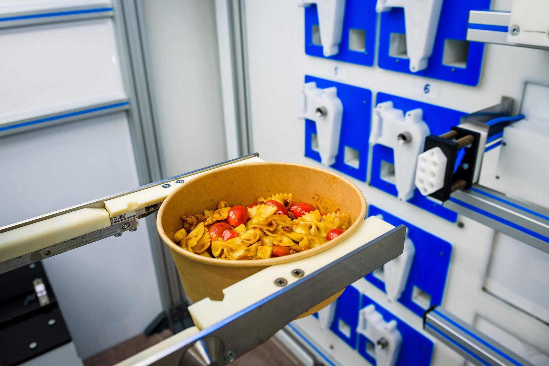 A robot holds a bowl with a pasta dish after preparation at the Roboeatz eatery in Riga, Latvia, May 25, 2021. (AFP Photo)