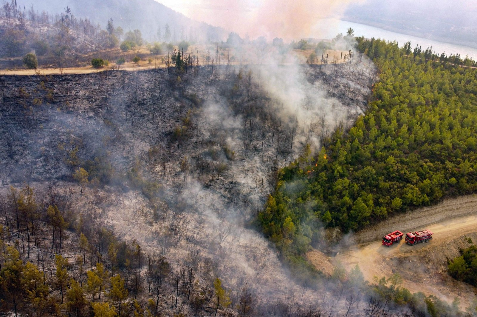 This aerial photograph shows firetrucks on a road as a wildfire engulfs a Mediterranean resort region on Turkey's southern coast near the town of Manavgat, on July 30, 2021.  (AFP Photo)