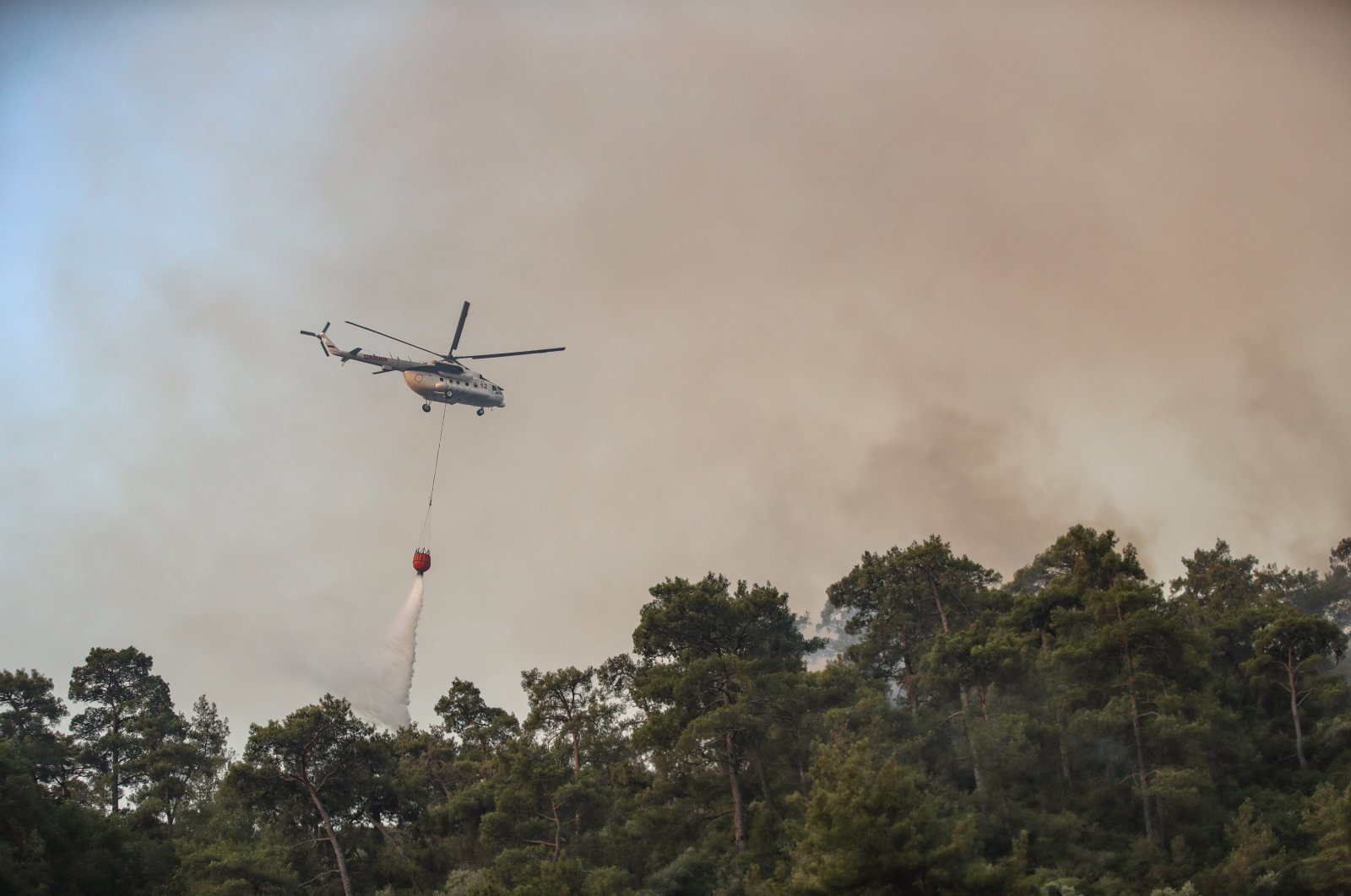 A helicopter douses a wildfire burning in a rural area of the Marmaris district of Mugla, Turkey, 31 July 2021. (EPA Photo)