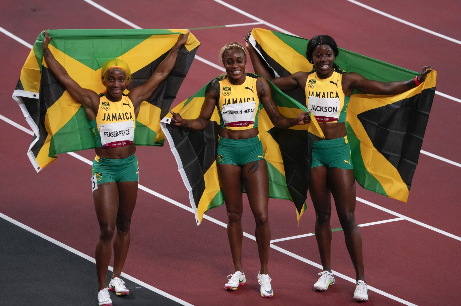 Elaine Thompson-Herah (C) of Jamaica, celebrates after winning the women's 100-meter final with Shelly-Ann Fraser-Pryce, of Jamaica, second place, and Shericka Jackson, of Jamaica, third, at the 2020 Summer Olympics, Saturday, July 31, 2021, in Tokyo. (AP Photo)
