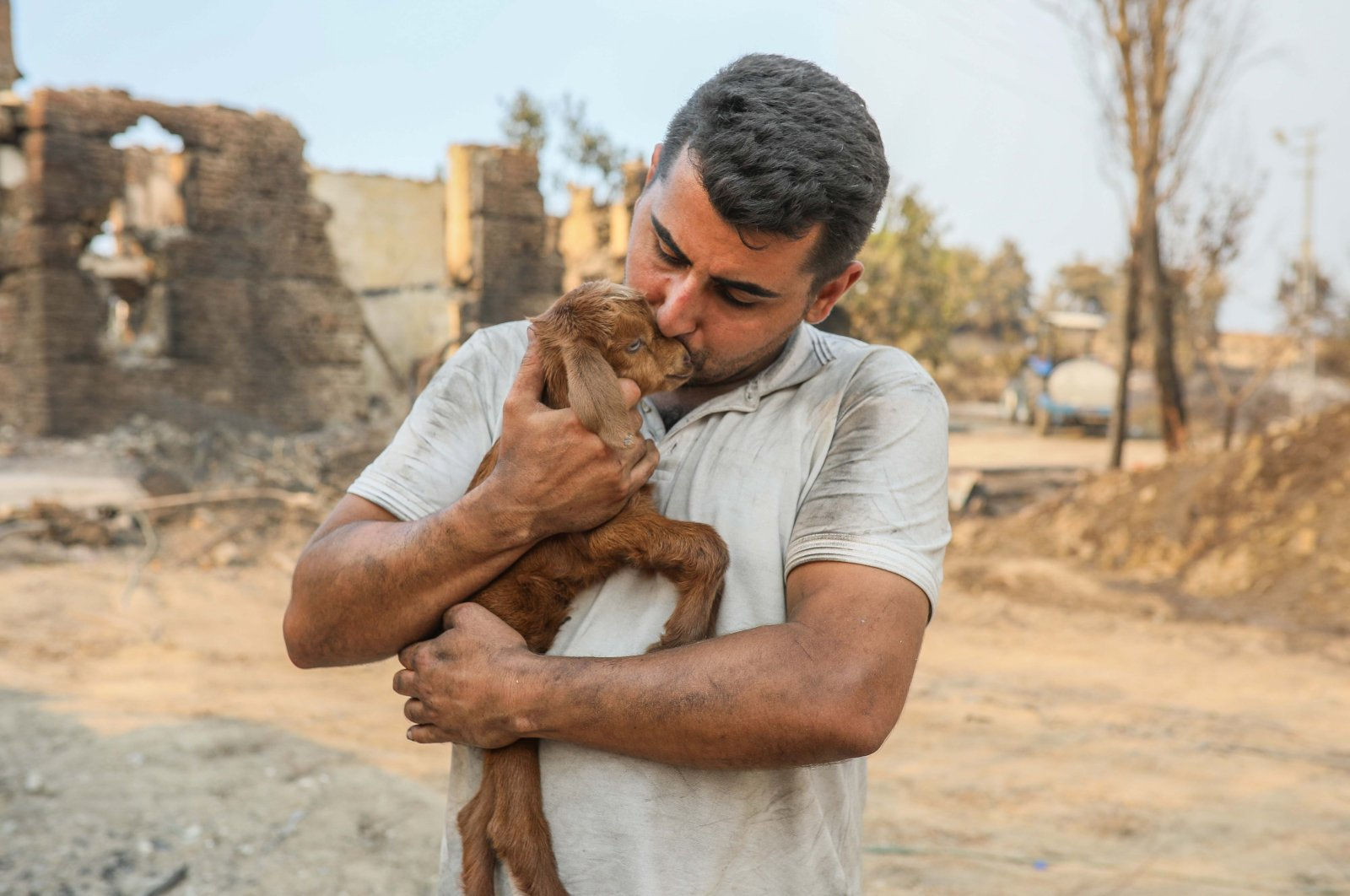 """Sercan Bayat holds a baby goat named """"Miracle"""" amid forest fires in Manavgat, Antalya province, Turkey, July 30, 2021. (DHA Photo)"""