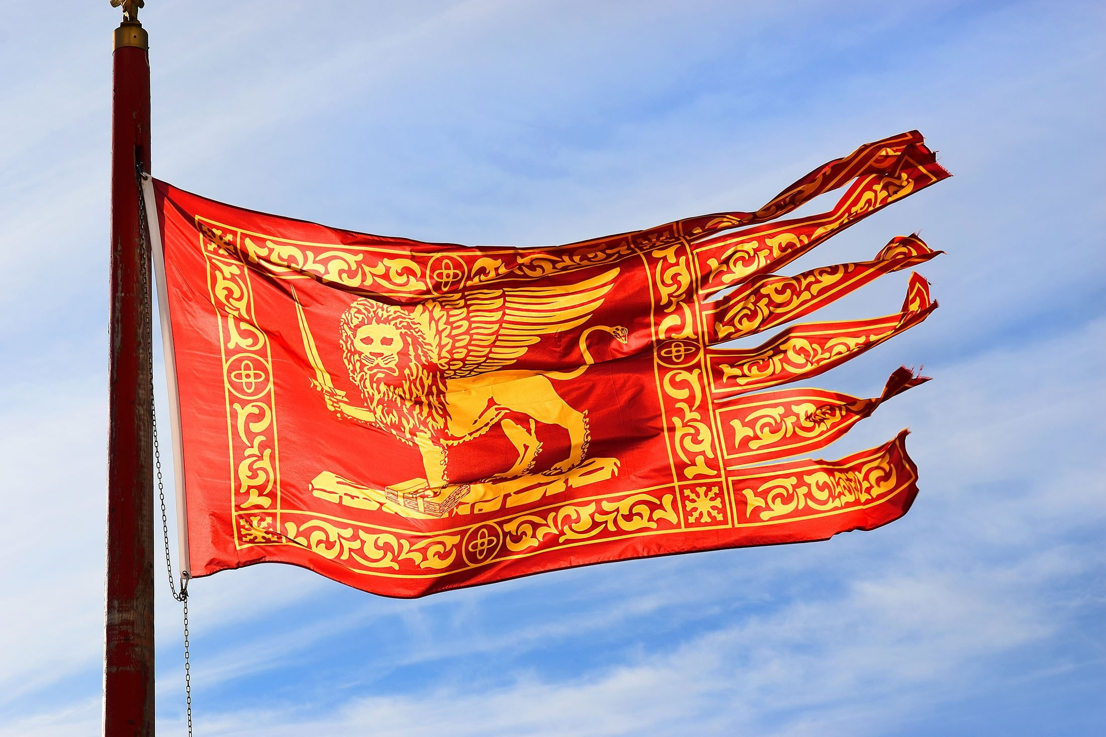 The Flag of the Republic of Venice, commonly known as the Standard of Saint Mark due to the Lion of Saint Mark on the flag, waves in the wind. (Shutterstock Photo)