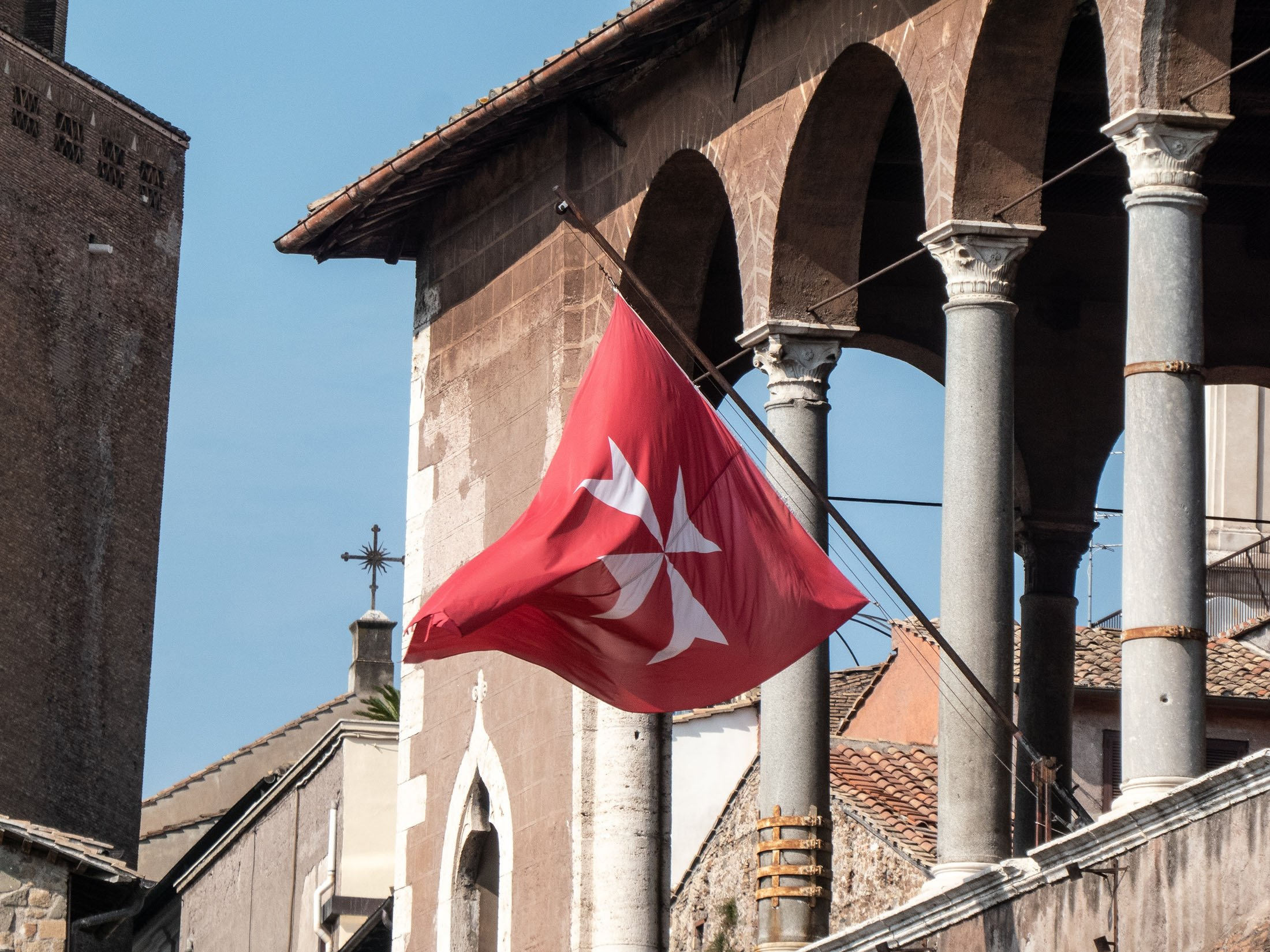 A flag of the Knights Hospitaller waves at theCasa dei Cavalieri di Rodi (House of the Knights of Rhodes),in the ruins of the Forum of Augustus, Rome, Italy, Aug. 10, 2018. (Shutterstock Photo)