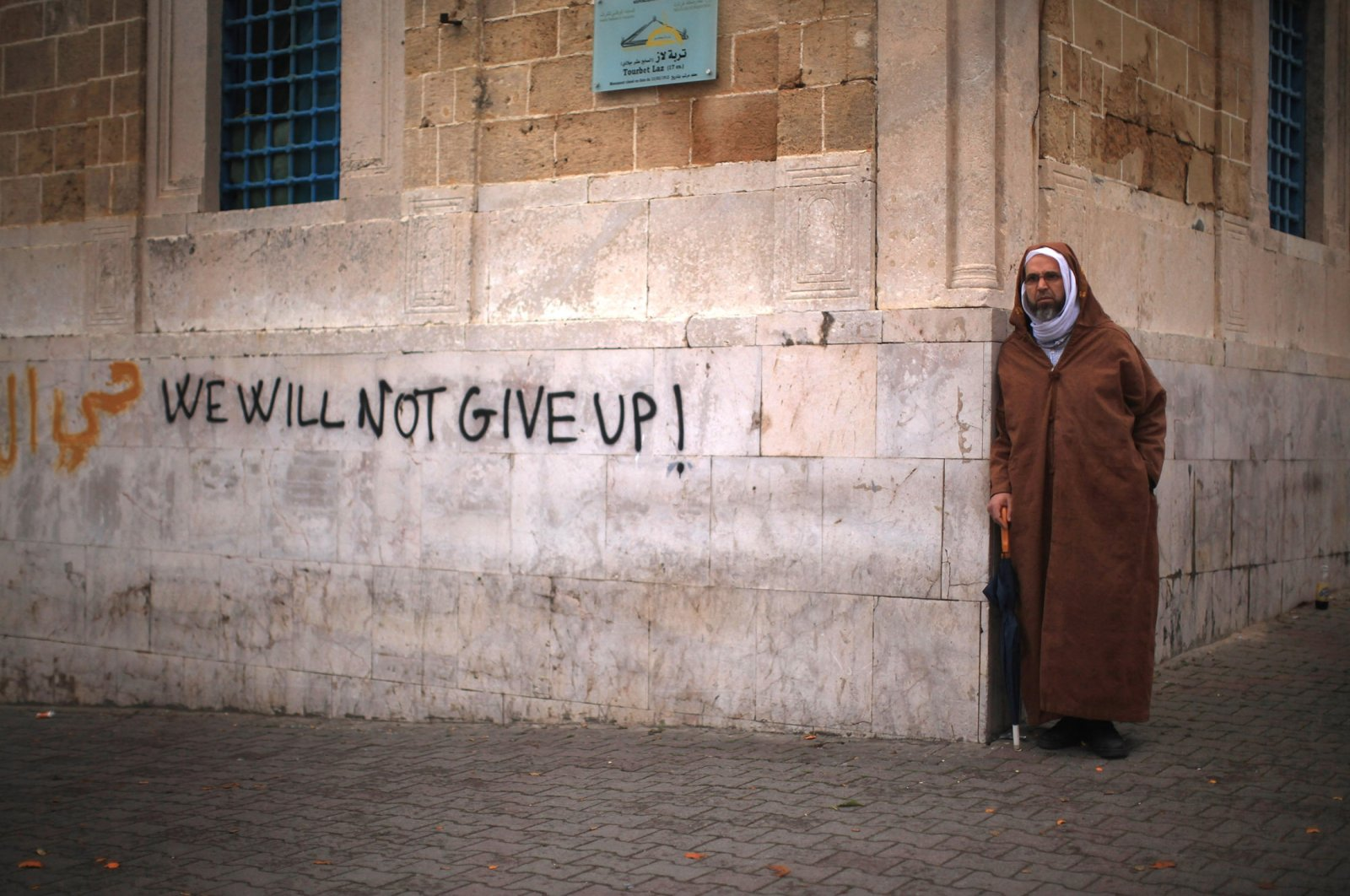 A Tunisian man looks on next to graffiti as protestors continue their demonstrations outside then-Prime Minister Mohammed Ghannouchi's offices in Tunis, Tunisia, Jan. 25, 2011. (Photo by Getty Images)