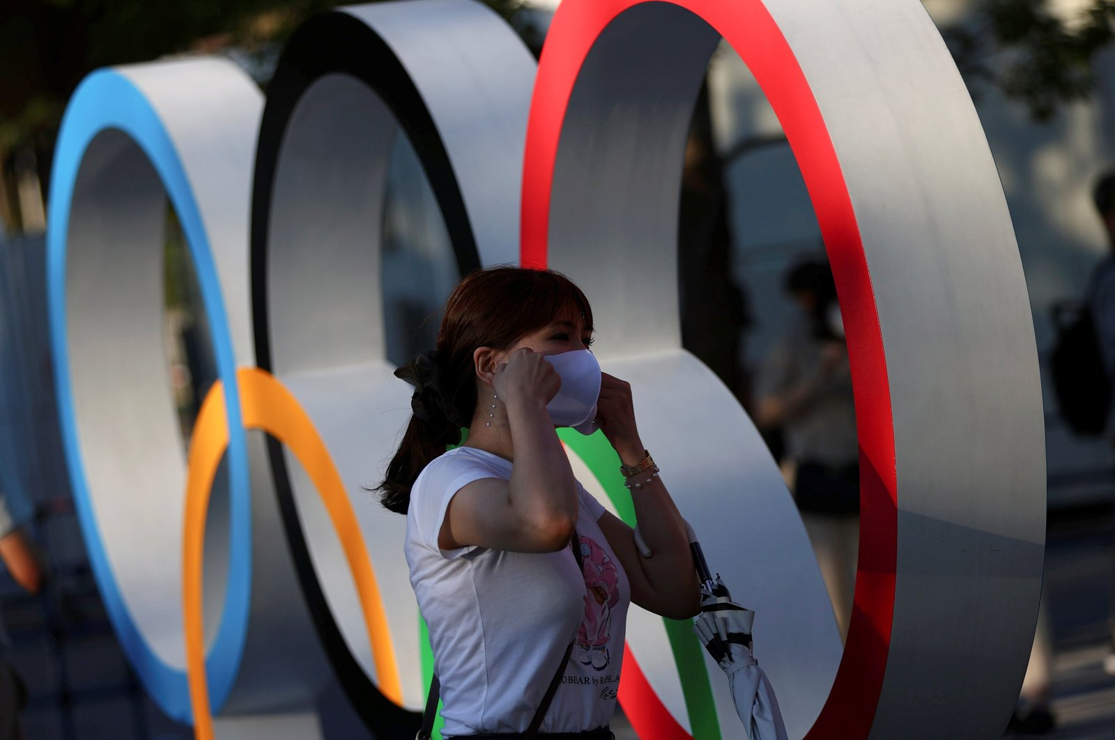 A woman adjusts her protective mask next to an Olympic rings monument outside the National Stadium, the main venue for the Tokyo 2020 Olympics amid the COVID-19 pandemic, Tokyo, Japan, July 31, 2021. (Reuters Photo)