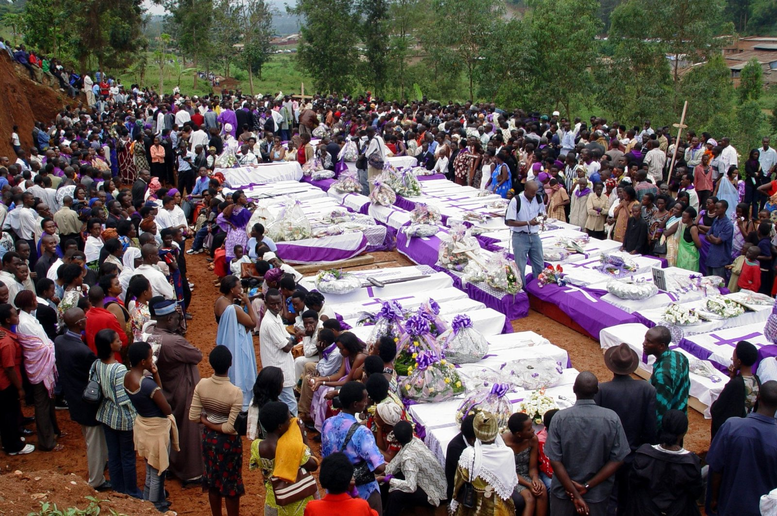 People pay their respects in front of dozens of coffins containing remains of more than 600 victims of the 1994 genocide, to be buried in mass graves during commemorations in the capital Kigali, Rwanda,  April 7, 2006. (Reuters Photo)