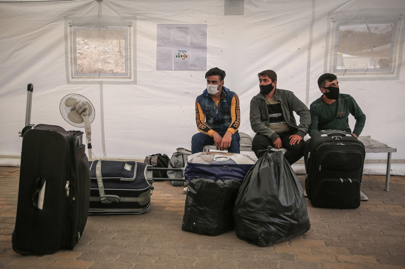 Syrians wearing face masks wait inside a mobile clinic at the Bab al-Hawa border crossing with Turkey, in Idlib, Syria, July 22, 2020. (Photo by Getty Images)