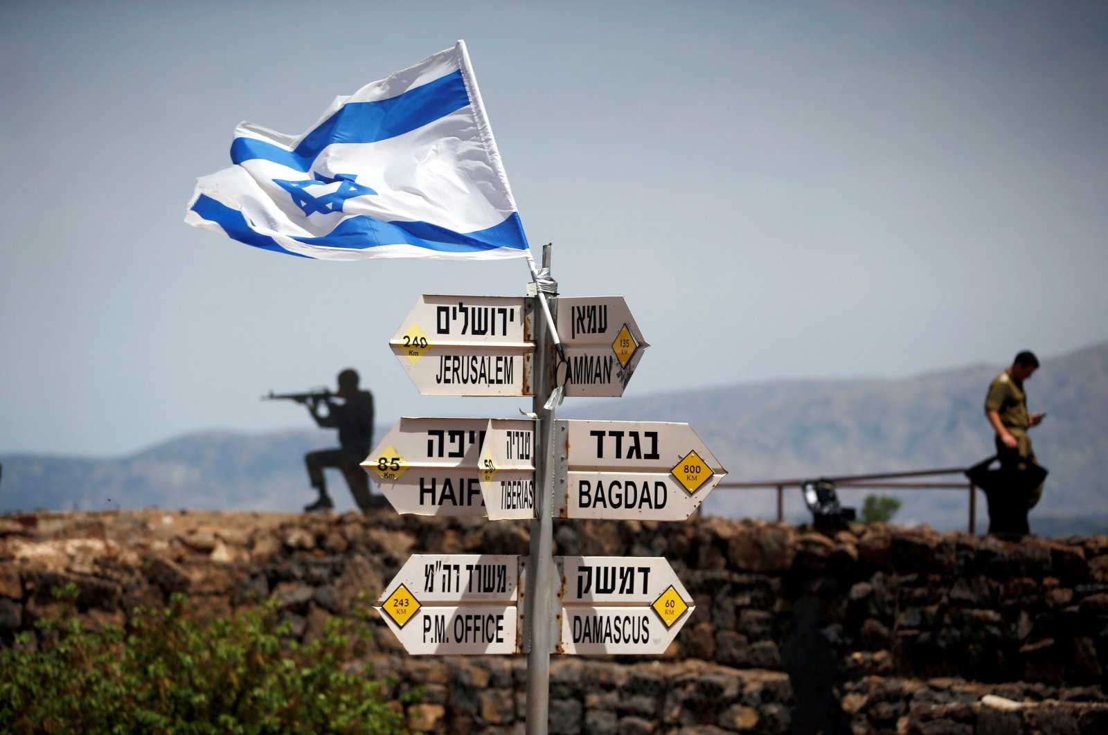 An Israeli soldier stands next to signs pointing out distances to different cities, on Mount Bental, an observation post that overlooks the Syrian side of the Quneitra crossing, Israeli-occupied Golan Heights, May 10, 2018. (Reuters Photo)