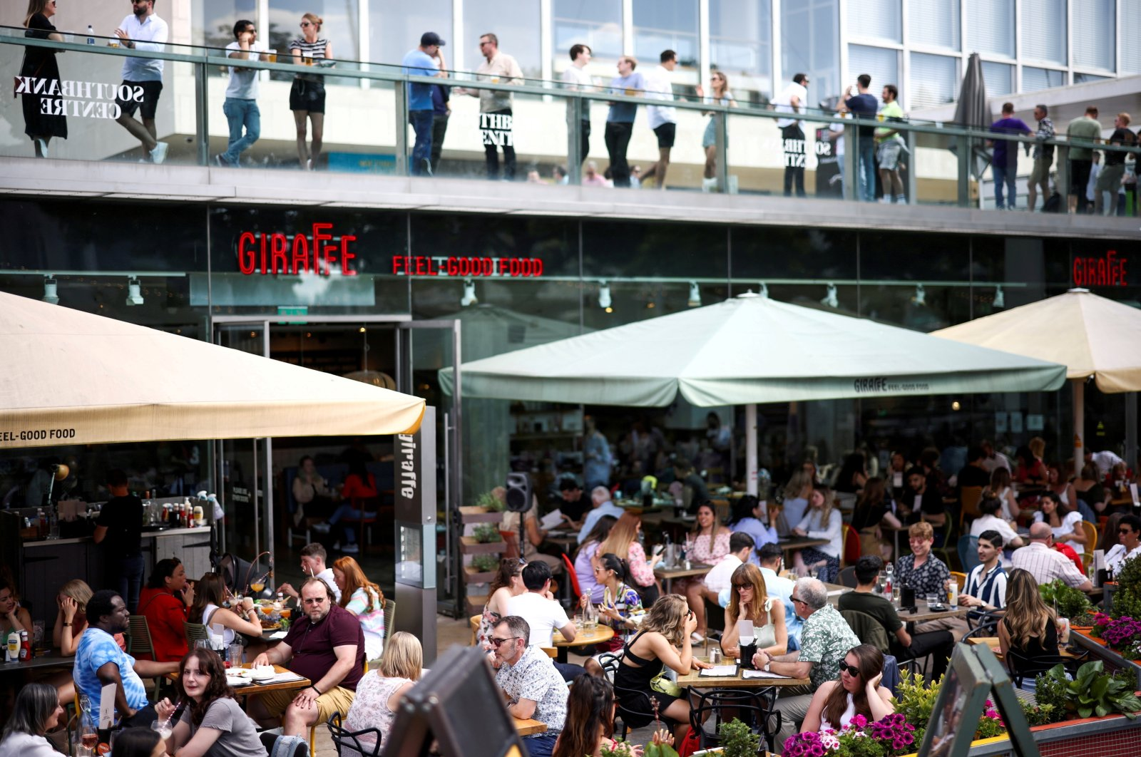 People sit at an outdoor restaurant on the South Bank during sunny weather in London, U.K., June 5, 2021. (Reuters Photo)
