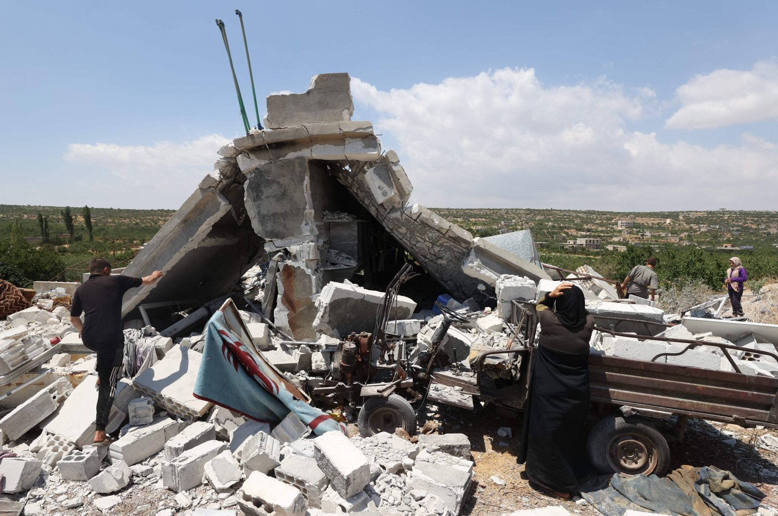 People salvage belongings from a house destoyed by a Russian missile attack in the Jabal al-Zawiya region in the south of Syria's opposition-held Idlib province, on July 4, 2021. (AFP Photo)