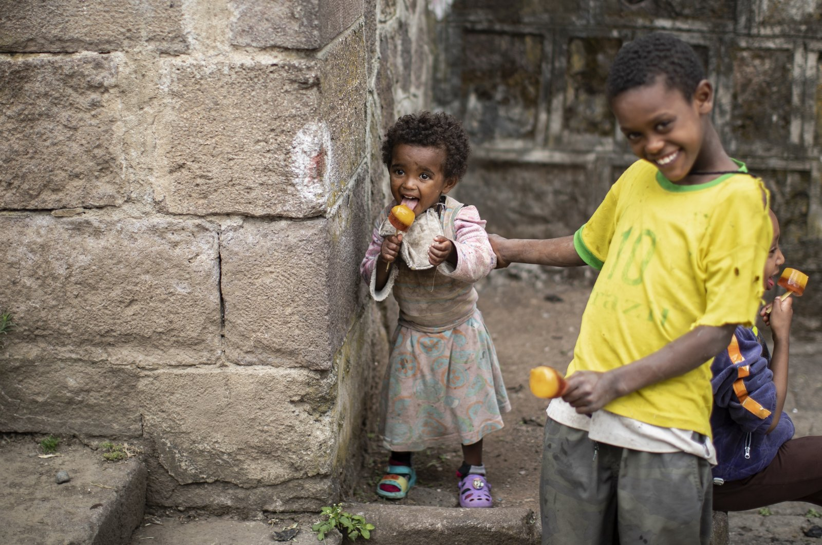 Children play and eat ice pops on a street in Gondar, in the Amhara region of northern Ethiopia, on May 1, 2021. (AP Photo)