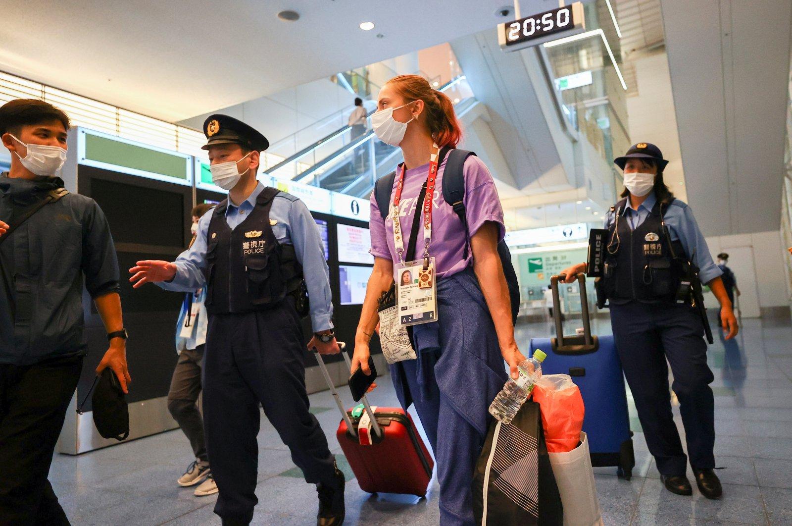 Belarusian athlete Krystsina Tsimanouskaya is escorted by police officers at Haneda international airport in Tokyo, Japan, Aug. 1, 2021.  (Reuters Photo)