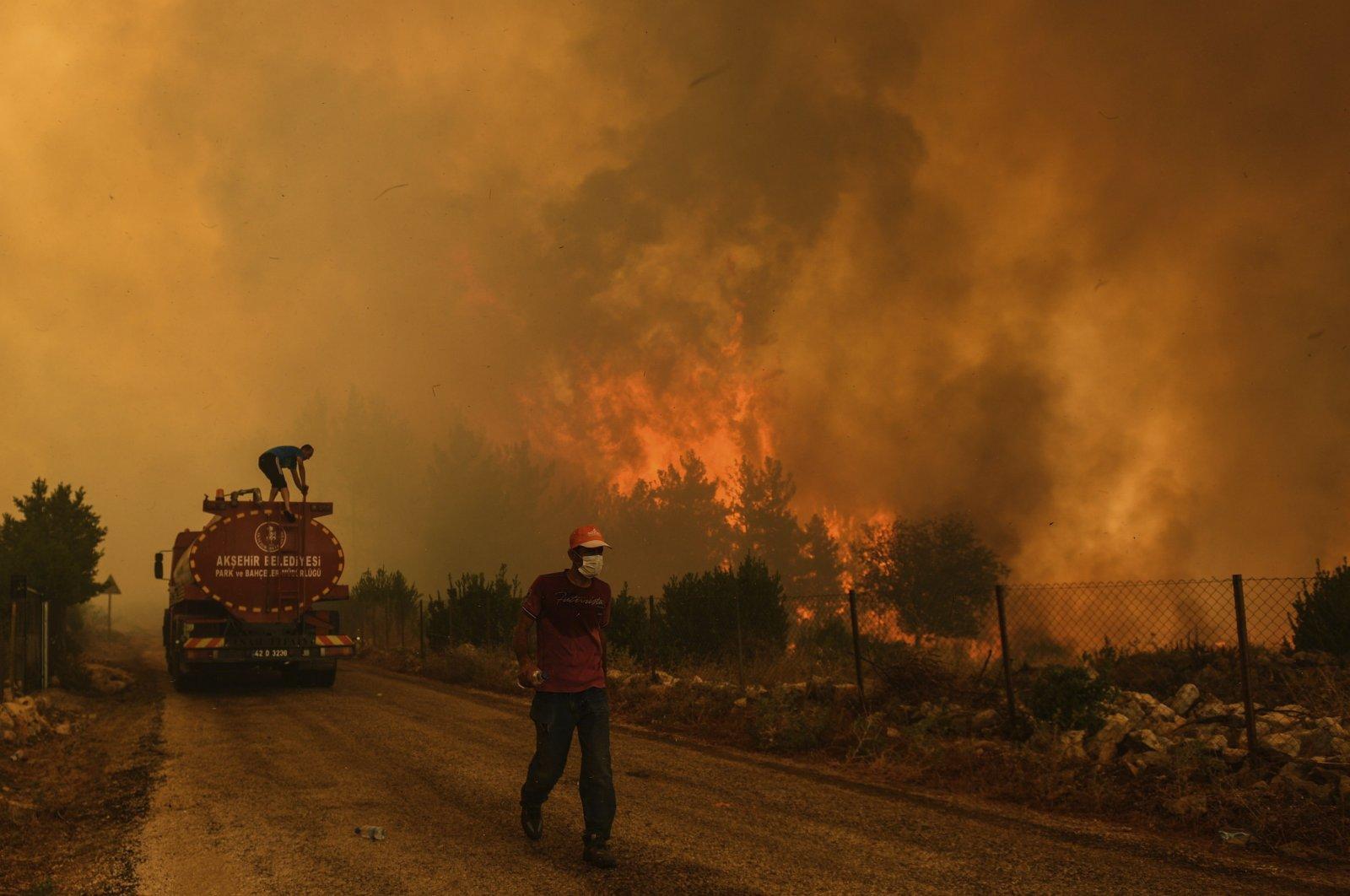 A man down a road in the fire-devastating Sirtköy village, near Manavgat, Antalya, Turkey, Sunday, Aug. 1, 2021. (AP Photo)