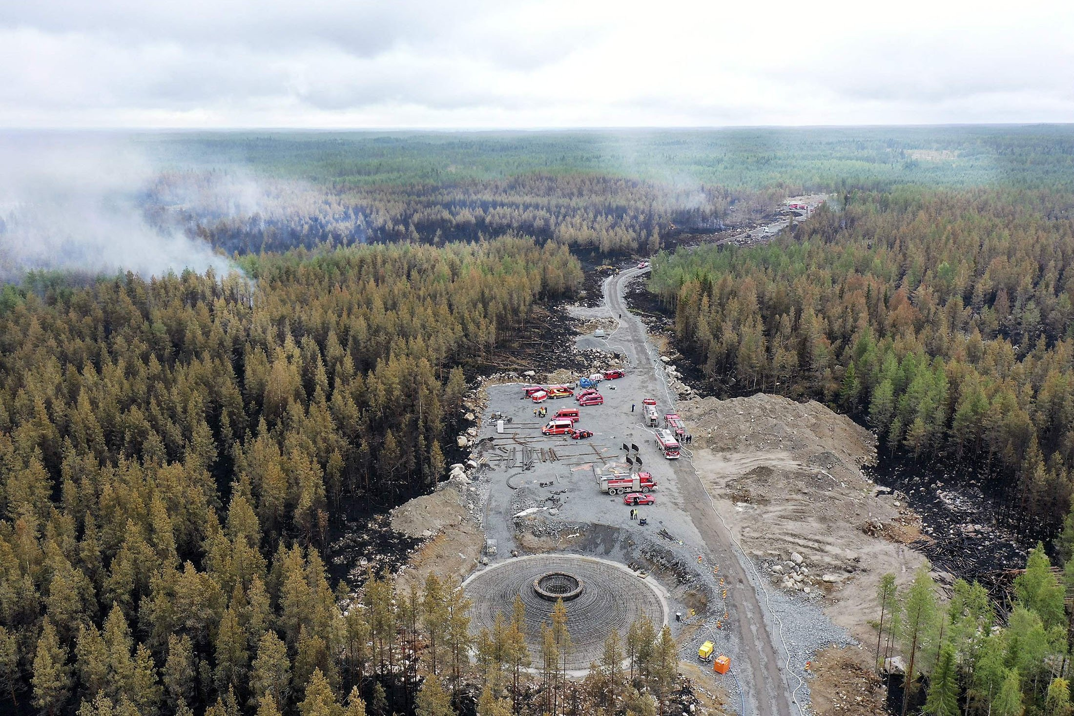 An aerial view shows smoke rising from the burned forest as firefighters and trucks work to extinguish a wildfire in Kalajoki, Northern Ostrobothnia region, north-western Finland, July 31, 2021. (AFP Photo)