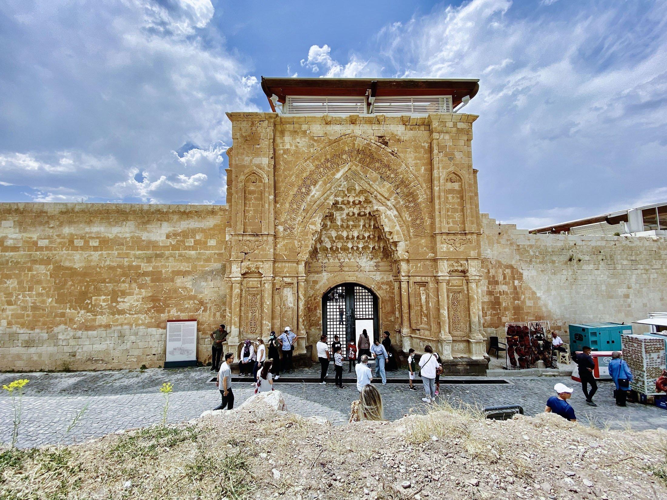 People walk through the grand main gate of the Ishak Pasha Palace can be seen from afar in theDoğubayazıt district of Ağrı, Turkey, July 30, 2021. (IHA Photo)
