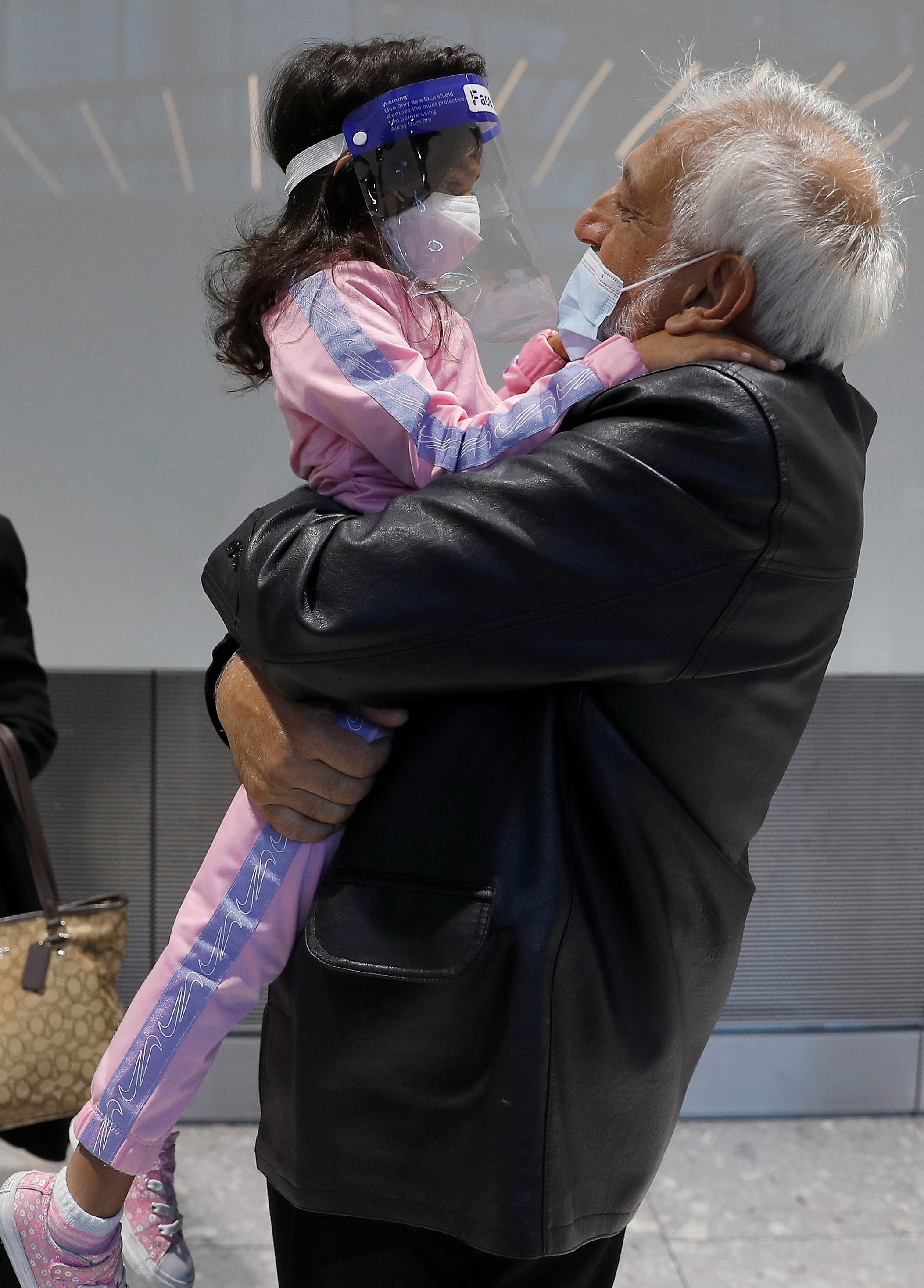 A man embraces his granddaughter after she arrives with family from Charlotte in the U.S., at the international arrivals area of Terminal 5 in London's Heathrow Airport, Britain, Aug. 2, 2021. (Reuters Photo)