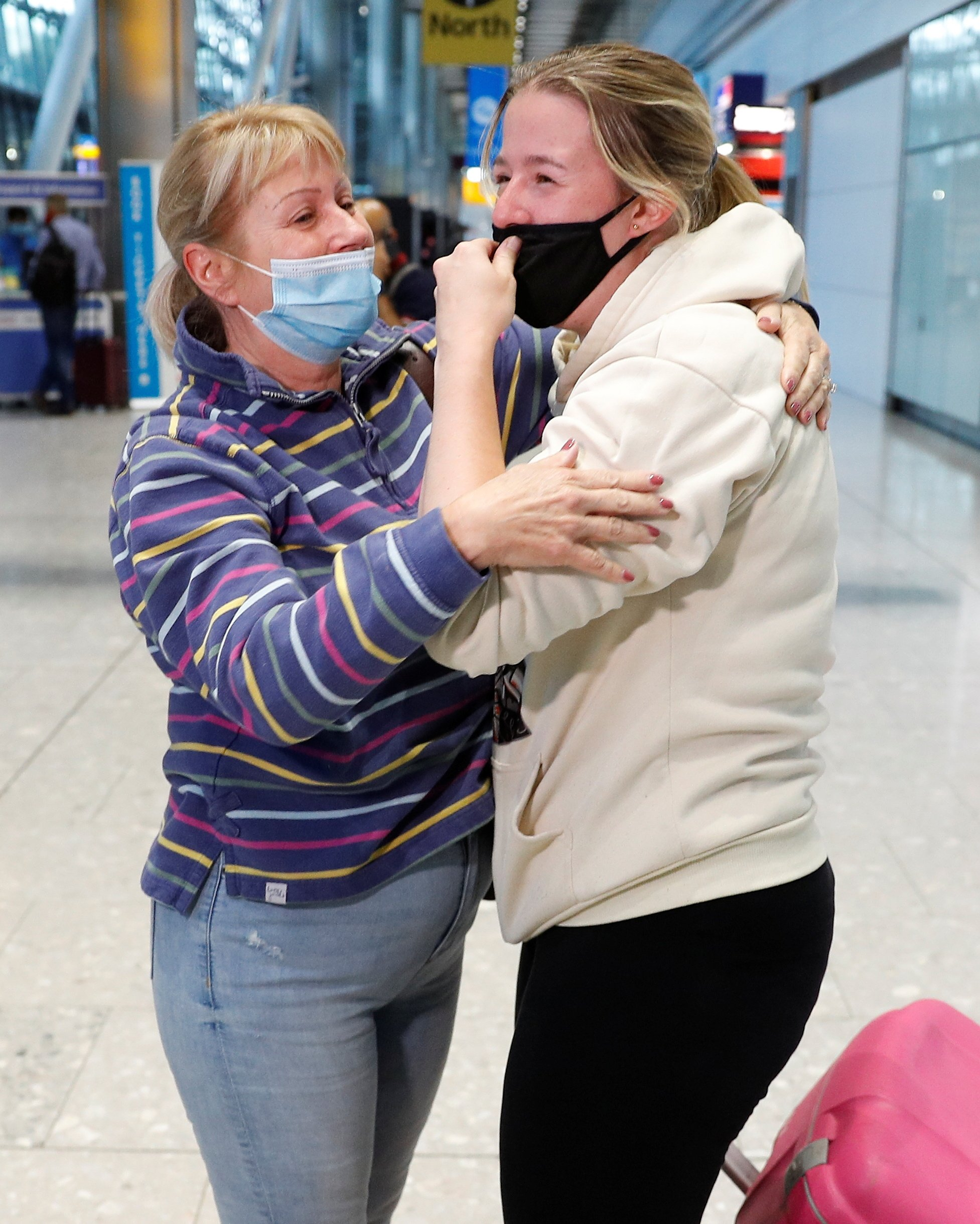 Claire Frohlich embraces her daughter who returned from the U.S., in the international arrivals area of Terminal 5 at London's Heathrow Airport, Britain, Aug. 2, 2021. (Reuters Photo)