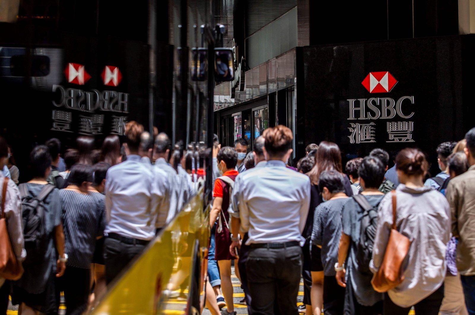 Pedestrians walk past the HSBC logo outside a local branch bank in Hong Kong, Aug. 2, 2021. (AFP Photo)