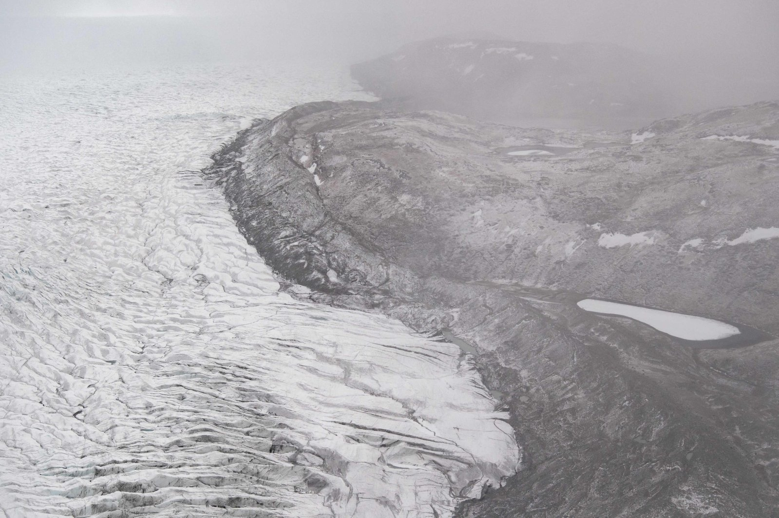 Ice recedes from a glacier as seen from an aerial helicopter tour with U.S. Secretary of State Antony Blinken of ice caps and fjords near Kangerlussuaq, Greenland, May 20, 2021. (AFP Photo)