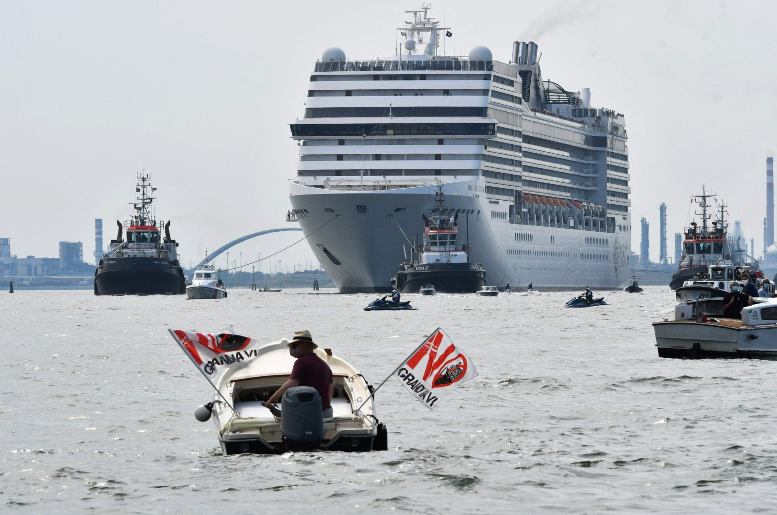 """Environmental protesters from the """"No Grandi Navi"""" (No Big Ships) group (L), demonstrate aboard a small boat against cruise ships in the lagoon, as the MSC Orchestra cruise ship leaves Venice across the basin, Venice, Italy, June 5, 2021. (AFP Photo)"""