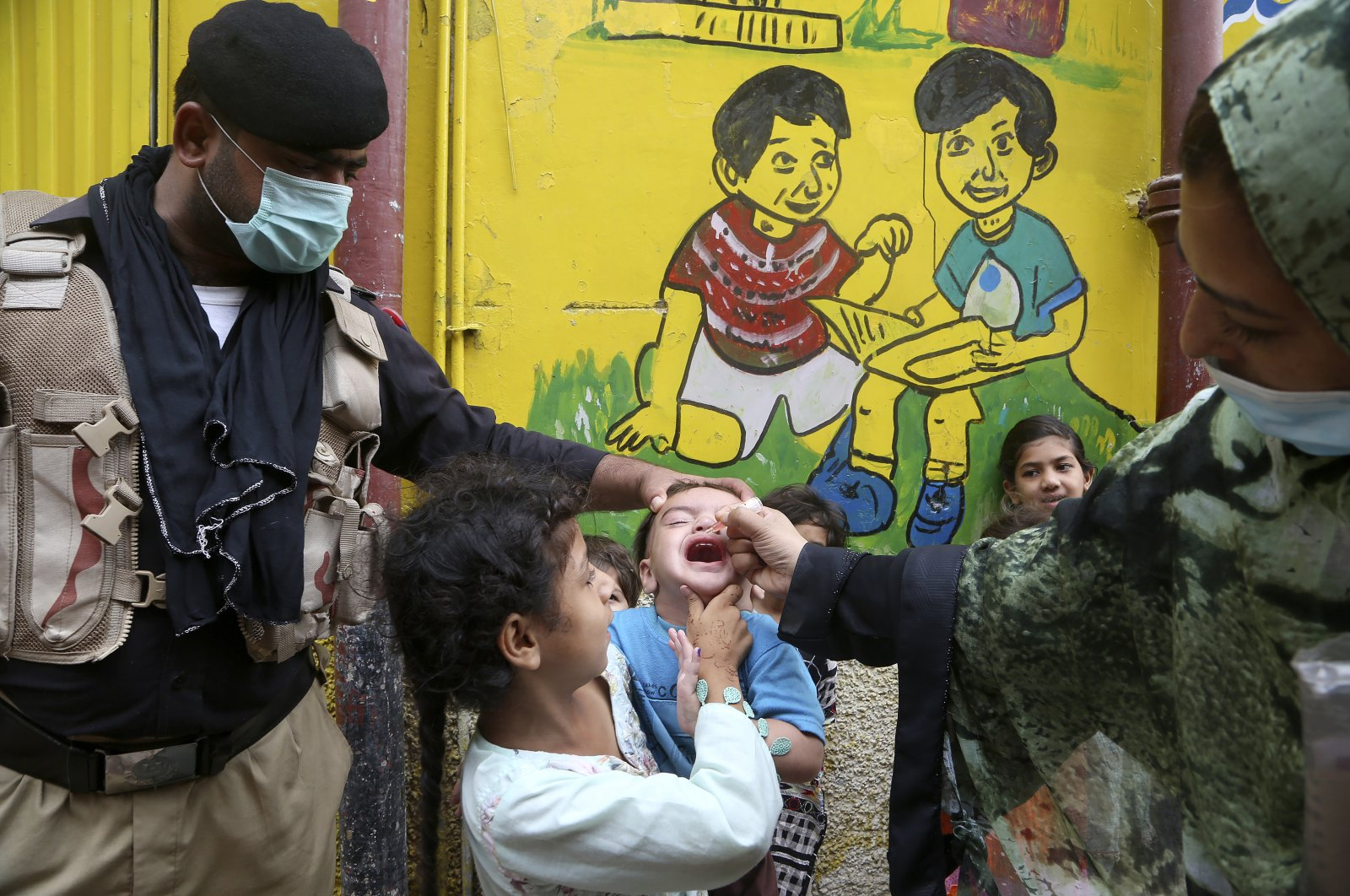 A police officer helps a health worker administer a polio vaccine to a child in Peshawar, Pakistan, on July 30, 2021. (AP Photo)