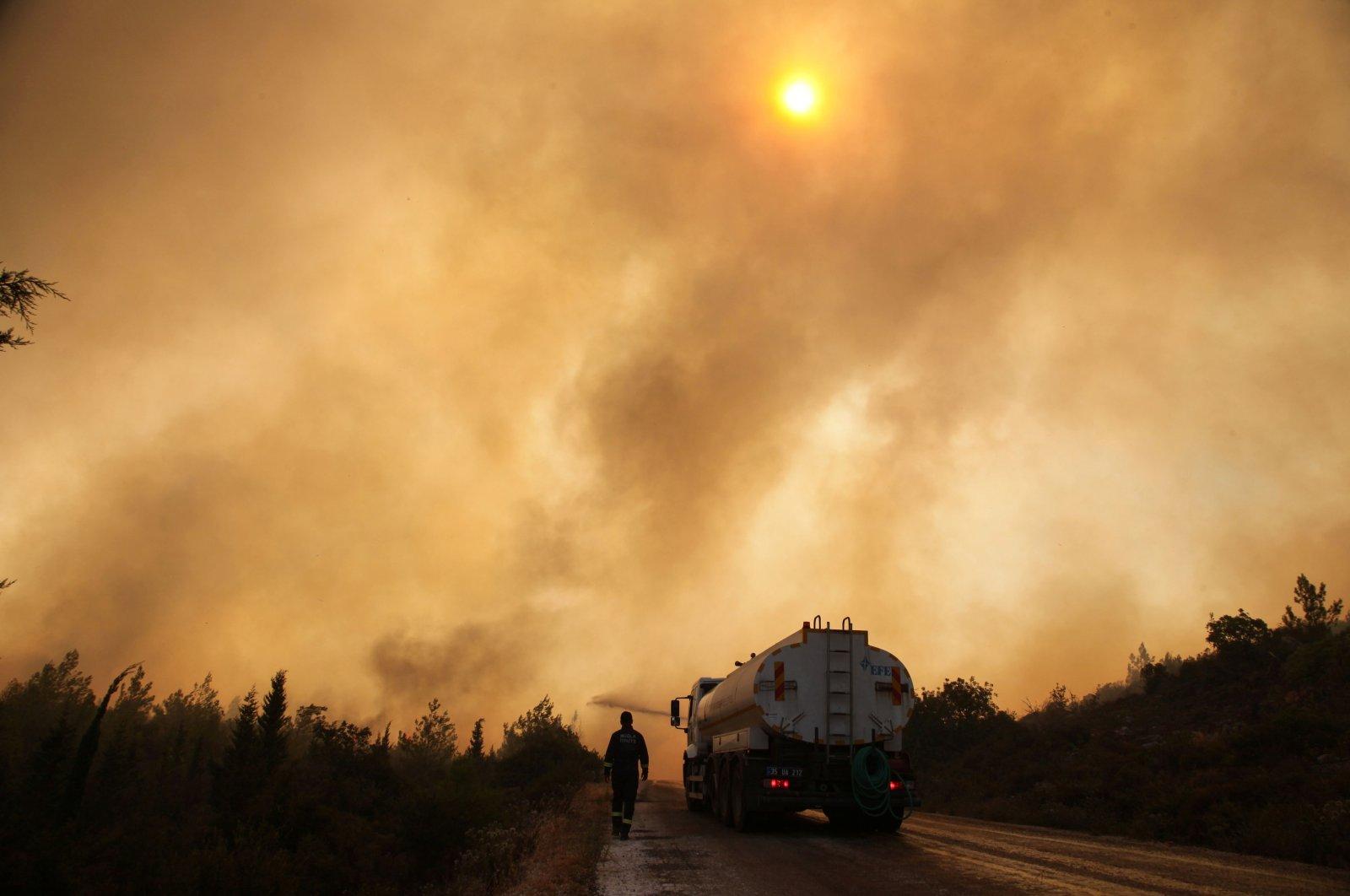 Firefighters extinguish a wildfire in the Mazı neighborhood near Bodrum, in Muğla, southwestern Turkey, August 2, 2021. (Reuters Photo)