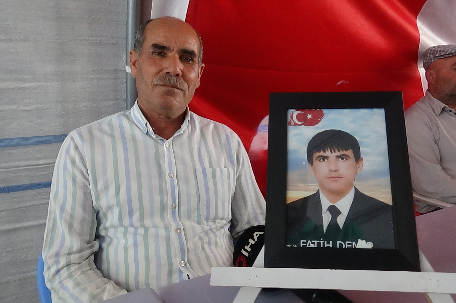 Father Abdullah Demir sits beside a picture of his son Fatih Demir in front of the pro-PKK HDP headquarters in southeastern Turkey, Aug. 2, 2021. (IHA Photo)
