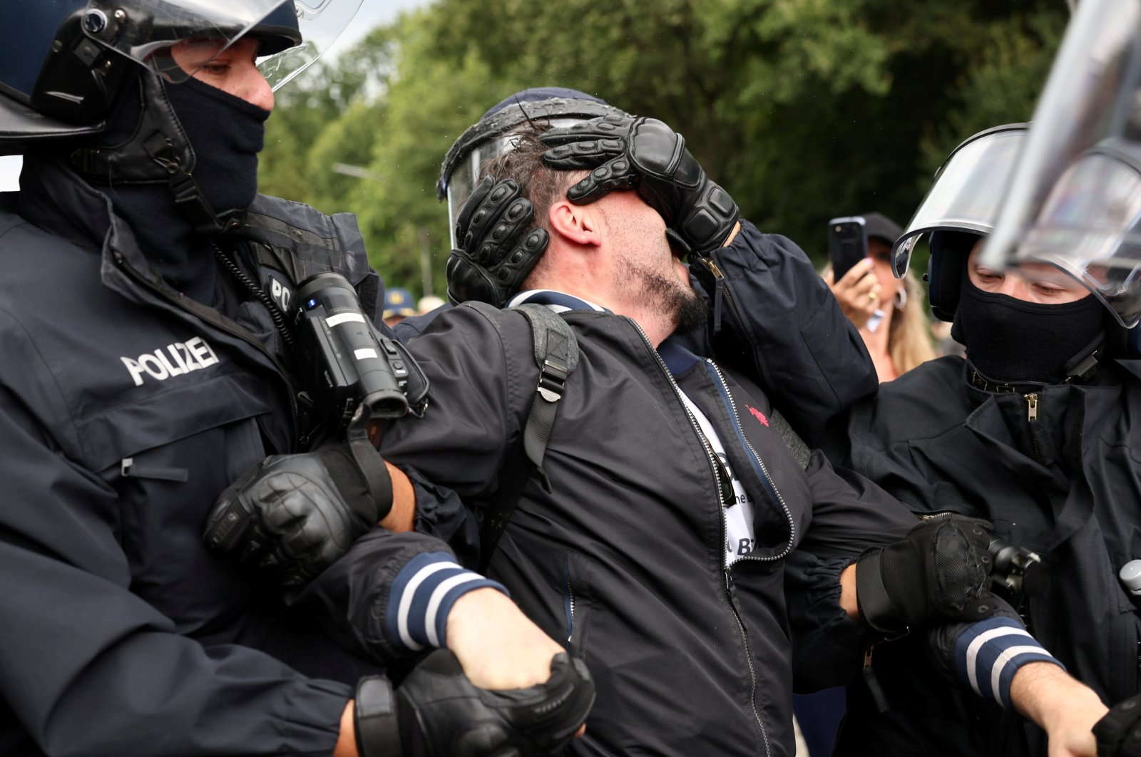 Police officers detain a demonstrator during a protest against government measures to curb the spread of coronavirus disease in Berlin, Germany Aug. 1, 2021. (Reuters Photo)