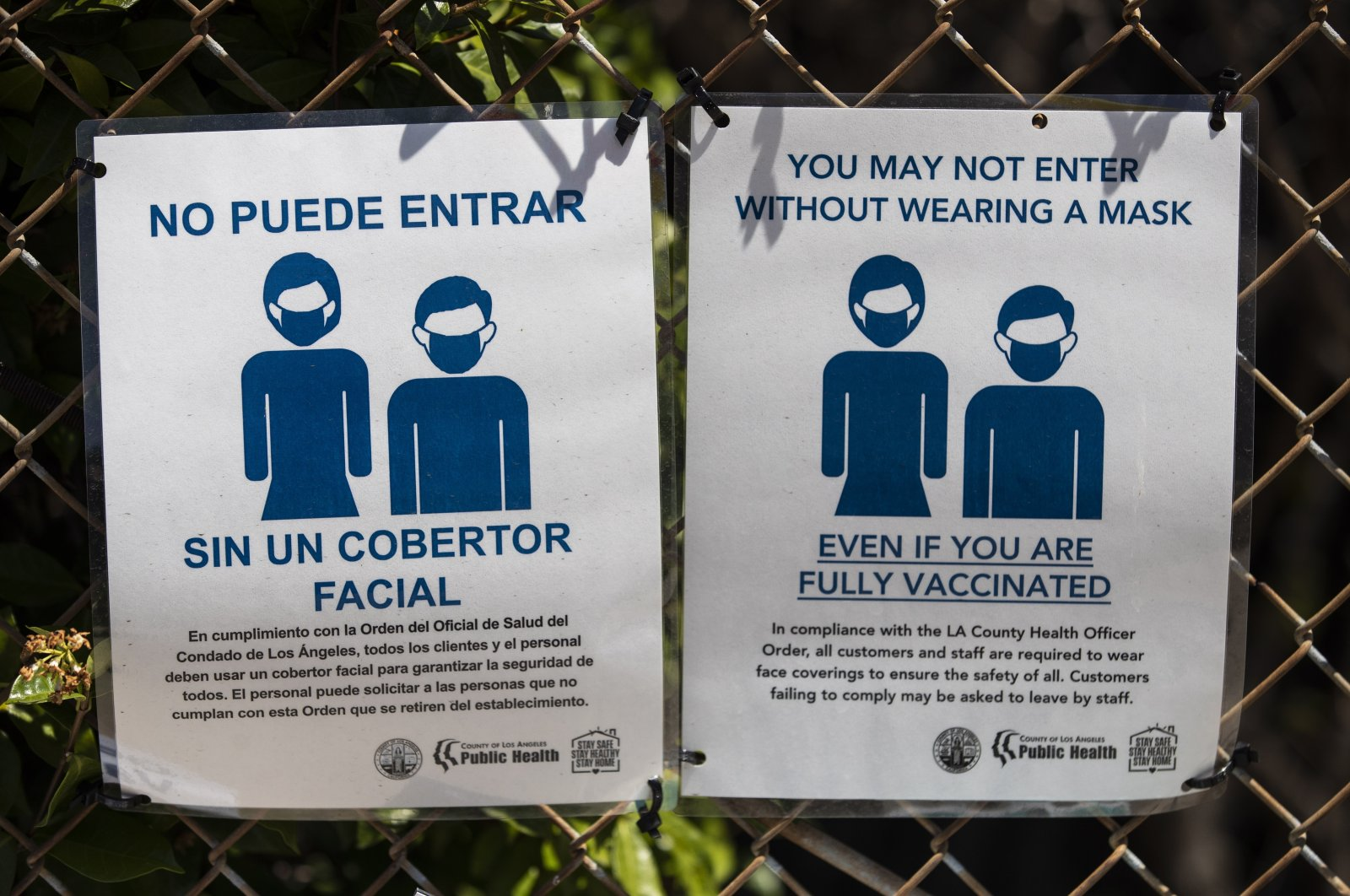 """A sign by the entrance of a COVID-19 vaccine clinic at the Para Los Ninos building organized by Walmart and Para Los Ninos reads """"You may not enter without wearing a mask even if you are fully vaccinated"""" in East Hollywood, California, U.S., 31 July 2021.  (EPA Photo)"""