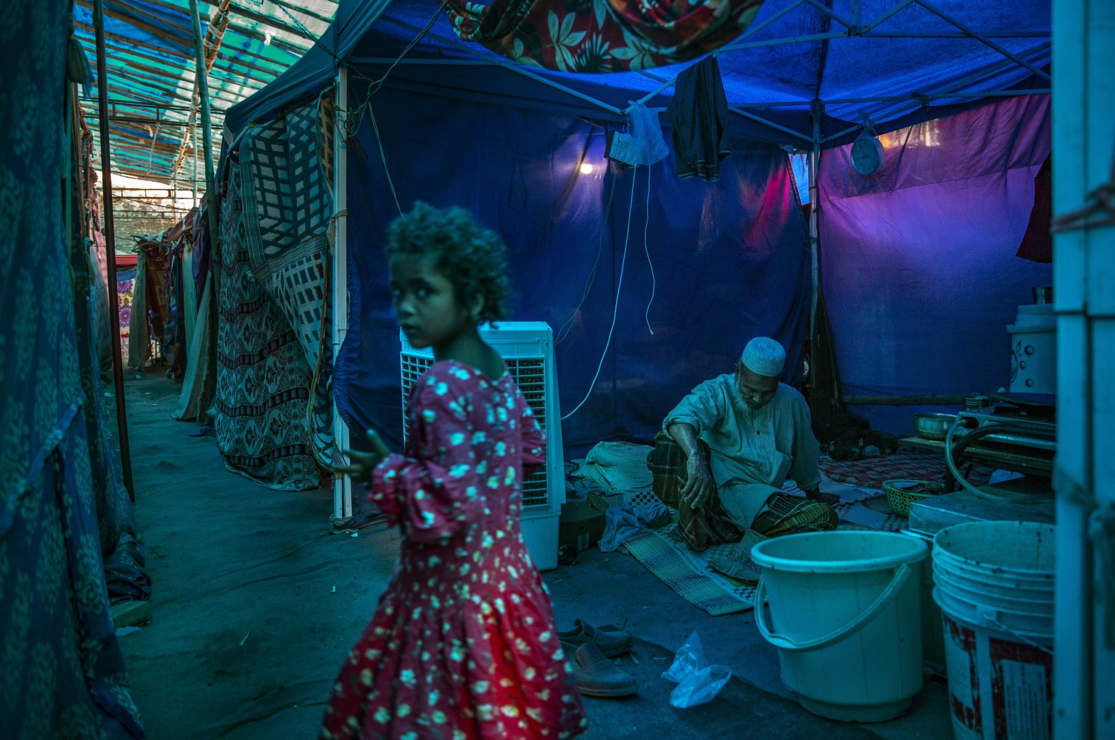 A young Rohingya refugee girl walks past an elderly man sitting inside a tent at a refugee camp alongside the banks of the Yamuna River on the southeastern border of New Delhi, India, July 1, 2021. (AP Photo)