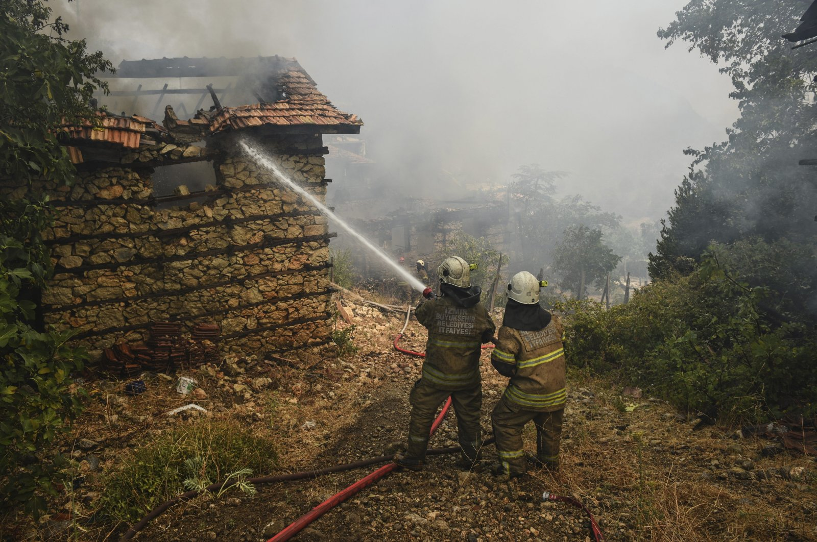 Firefighters water to stop a fire in the fire-devastating Sirtkoy village, near Manavgat, Antalya, Turkey, Sunday, Aug. 1, 2021. (AP Photo)