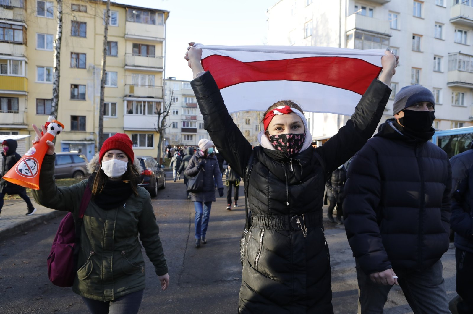 Demonstrators wearing face masks to help curb the spread of the coronavirus, wave an old Belarusian national flag, during an opposition rally to protest the official presidential election results in Minsk, Belarus, Sunday, Dec. 6, 2020. (AP File Photo)