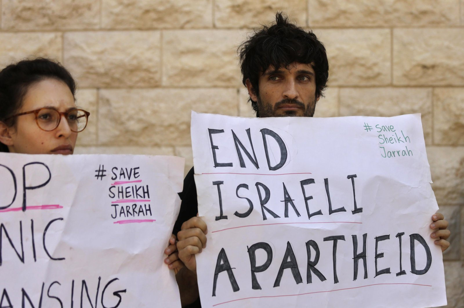 Protesters hold signs during a hearing on the possible evictions of Palestinians from Palestine's Sheikh Jarrah neighborhood in occupied East Jerusalem, outside the Israeli Supreme Court, West Jerusalem, Israel, Monday, Aug. 2, 2021. (AP Photo)