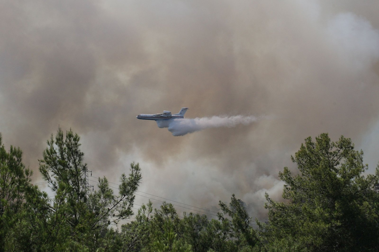 A firefighting aircraft drops water while extinguishing a forest fire near Marmaris, Turkey, July 30, 2021. (Reuters Photo)