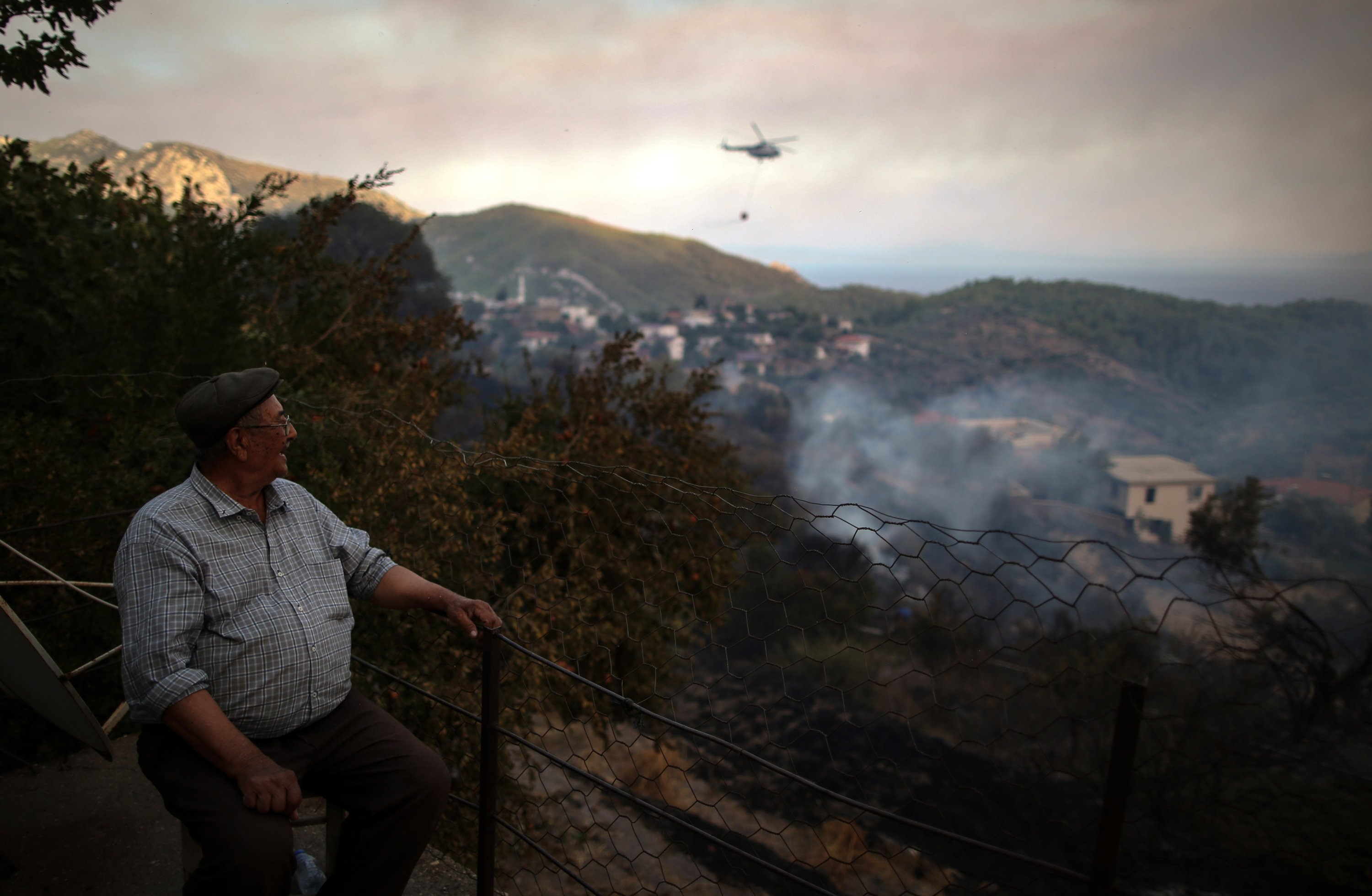 A man watches forest fires burn from his balcony in Bozdoğan village in Milas district in Muğla, Turkey on August 2, 2021 (EPA Photo)
