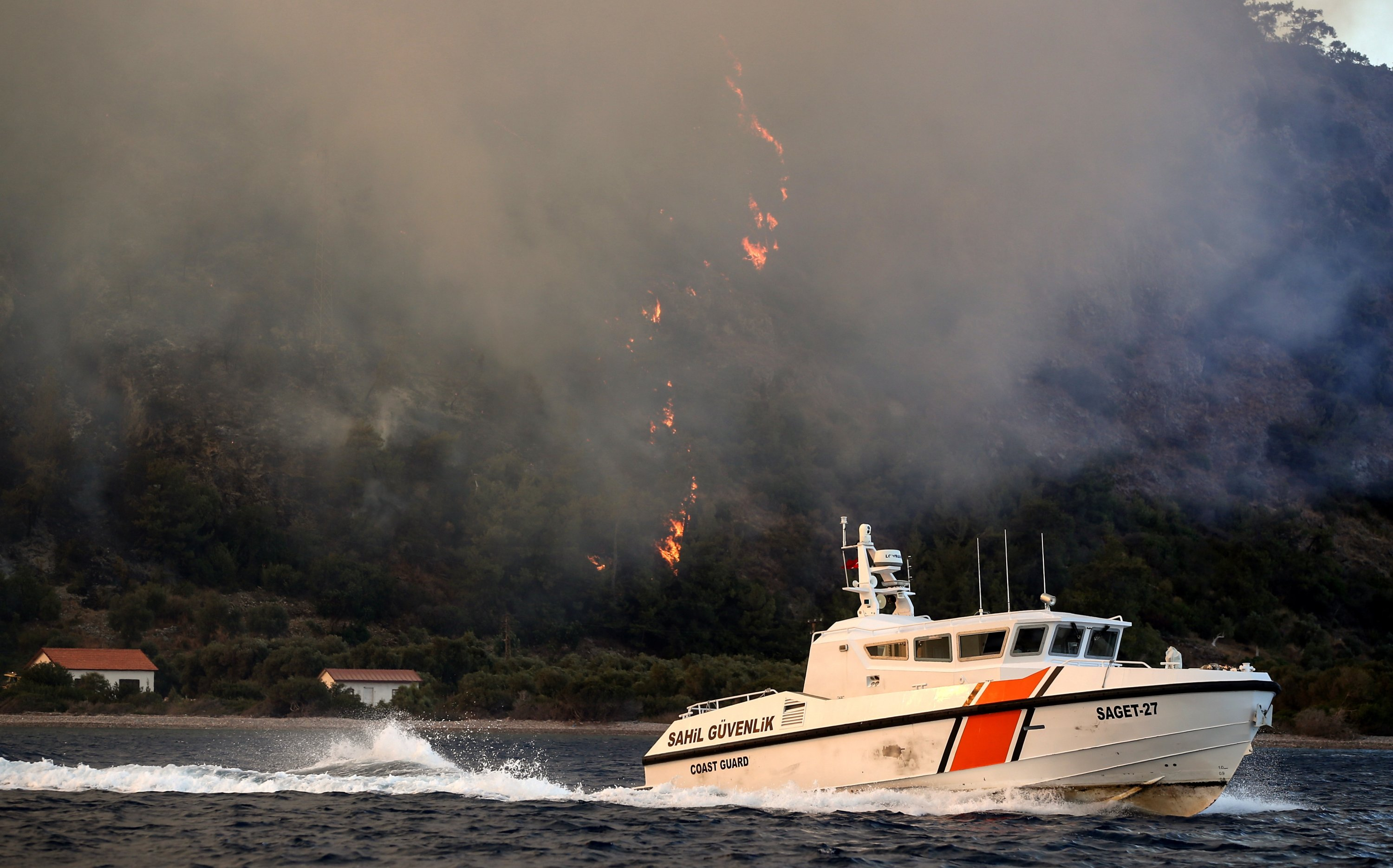 A Turkish Coast Guard boat walks past a burning forest fire in a rural area of Milas district in Muğla, Turkey on August 2, 2021 (EPA Photo)