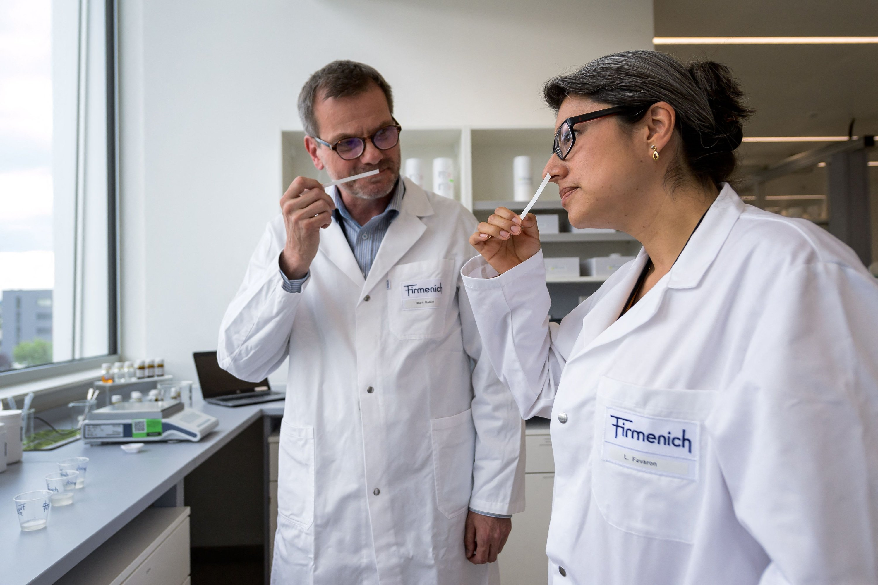 Flavorists Liliana Favaron (R) and Mark Rubin (L) smell a combination of fragrances at the headquarters of Swiss group Firmenich, in Satigny near Geneva, Switzerland, on June 30, 2021. (AFP Photo)