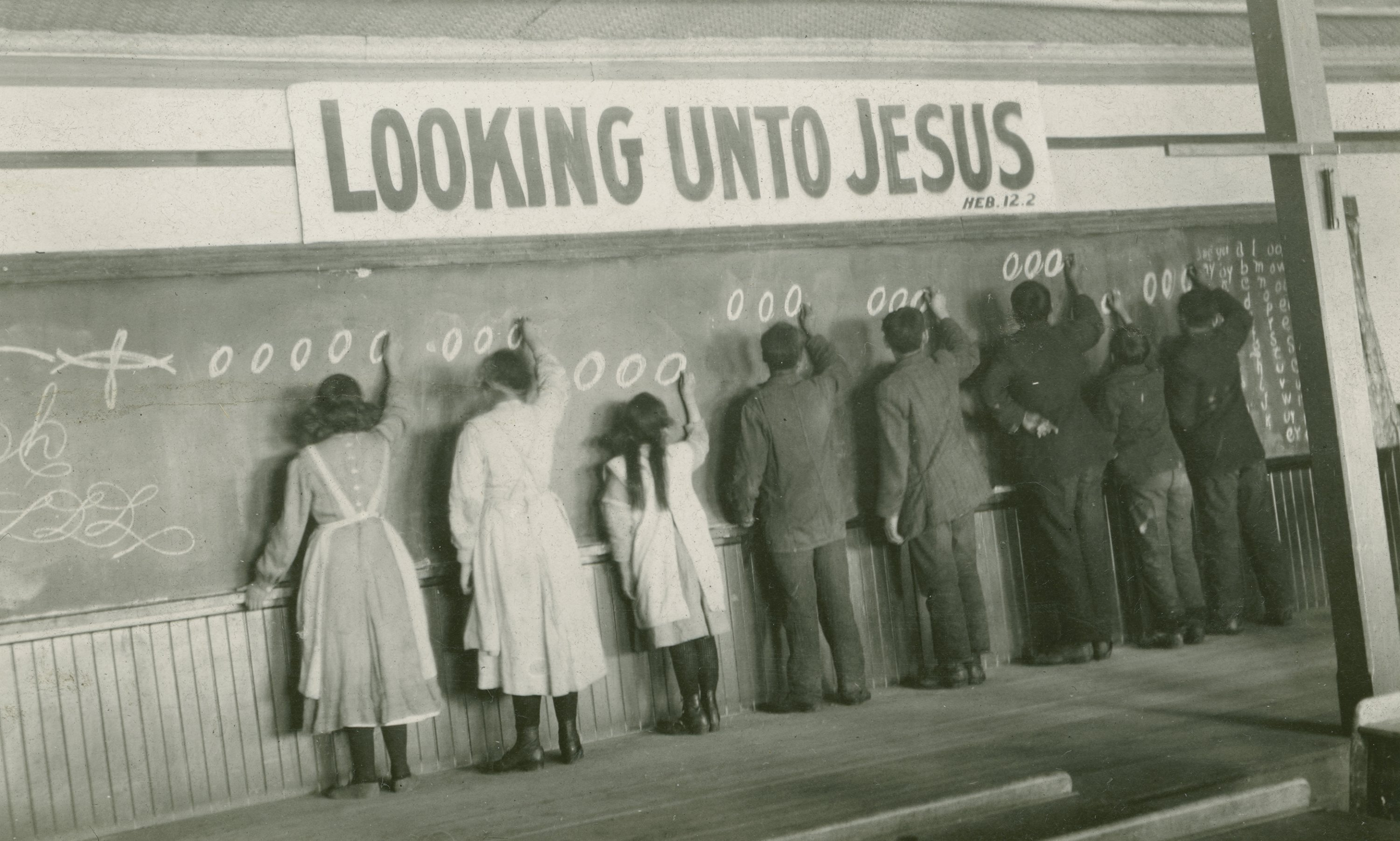 Students write on a chalkboard at the Red Deer Indian Industrial School in Alberta, Canada, in the 1910s. (AP Photo)