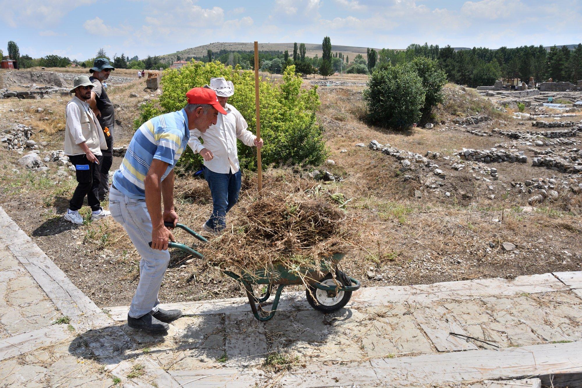 An official helps clear weeds in Alacahöyük, Çorum, central Turkey, on August 3, 2021. (AA Photo)