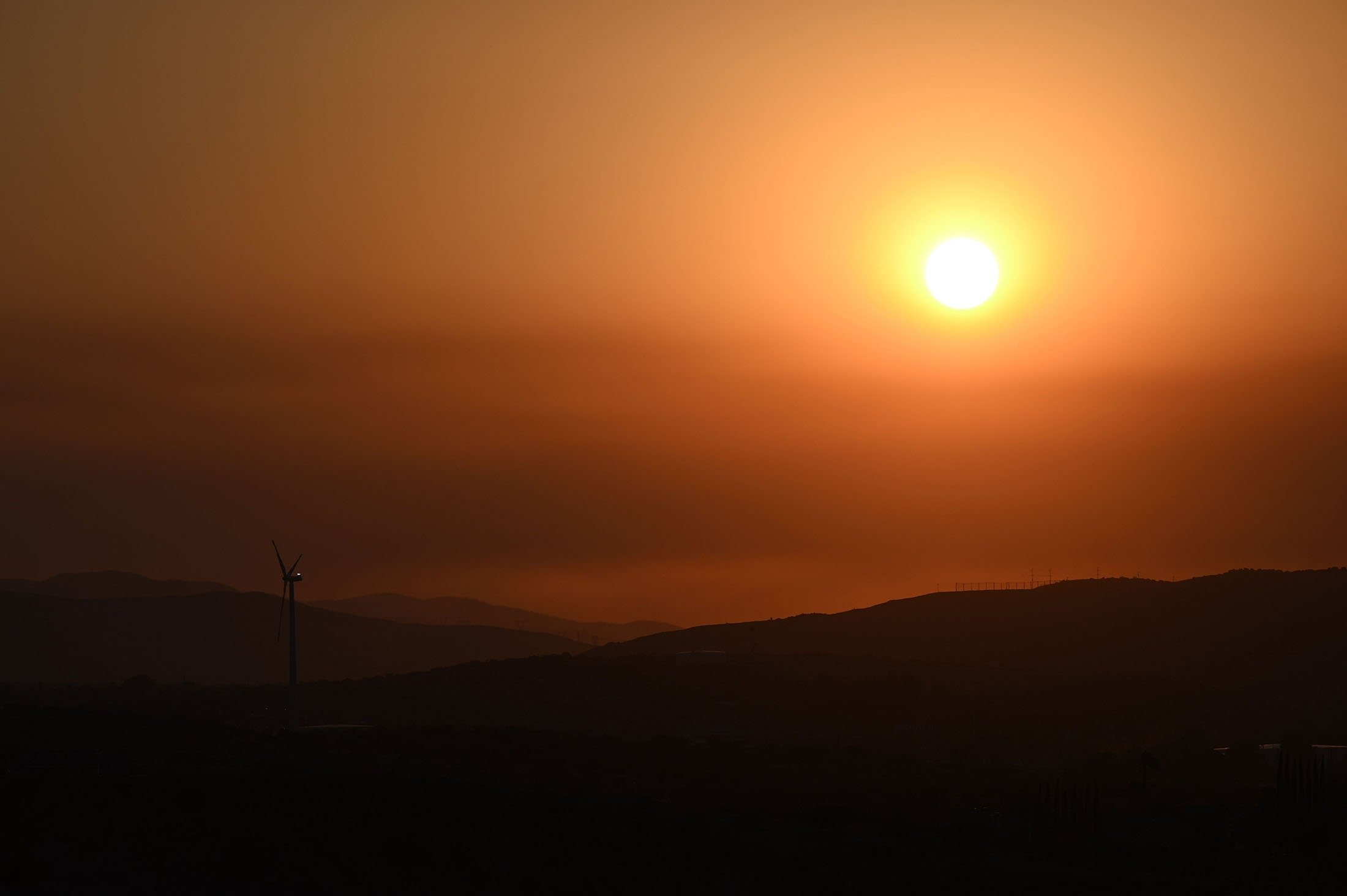 The sun sets near a windmill in Palmdale, where temperatures reached 41.1 degrees Celsius (106 degree Fahrenheit), California, U.S., July 12, 2021. (AFP Photo)