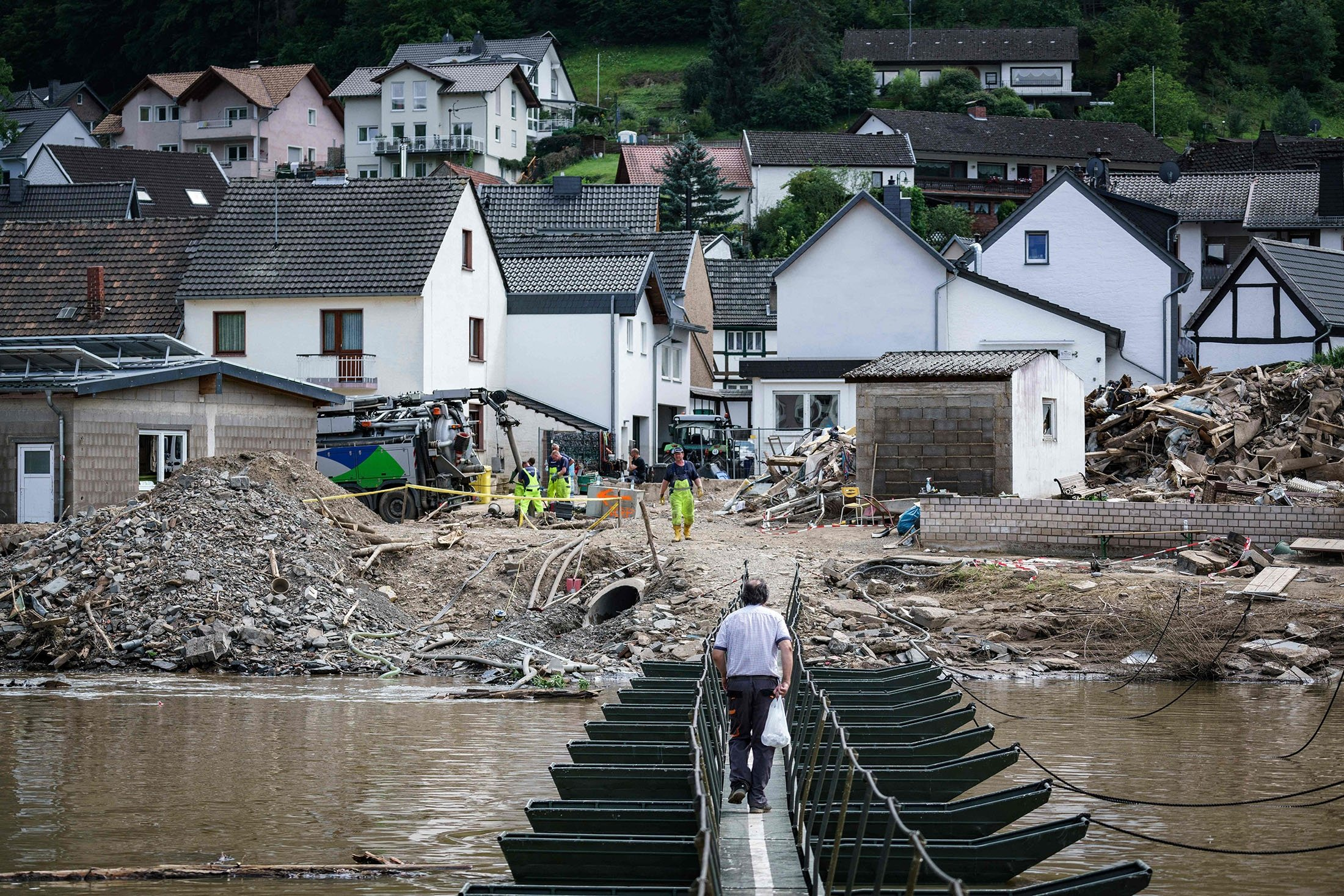 A man walks across a temporary bridge in the wine village of Rech near Dernau on the river Ahr, weeks after heavy rain and floods caused major damage in the Ahr region, western Germany, July 30, 2021. (AFP Photo)