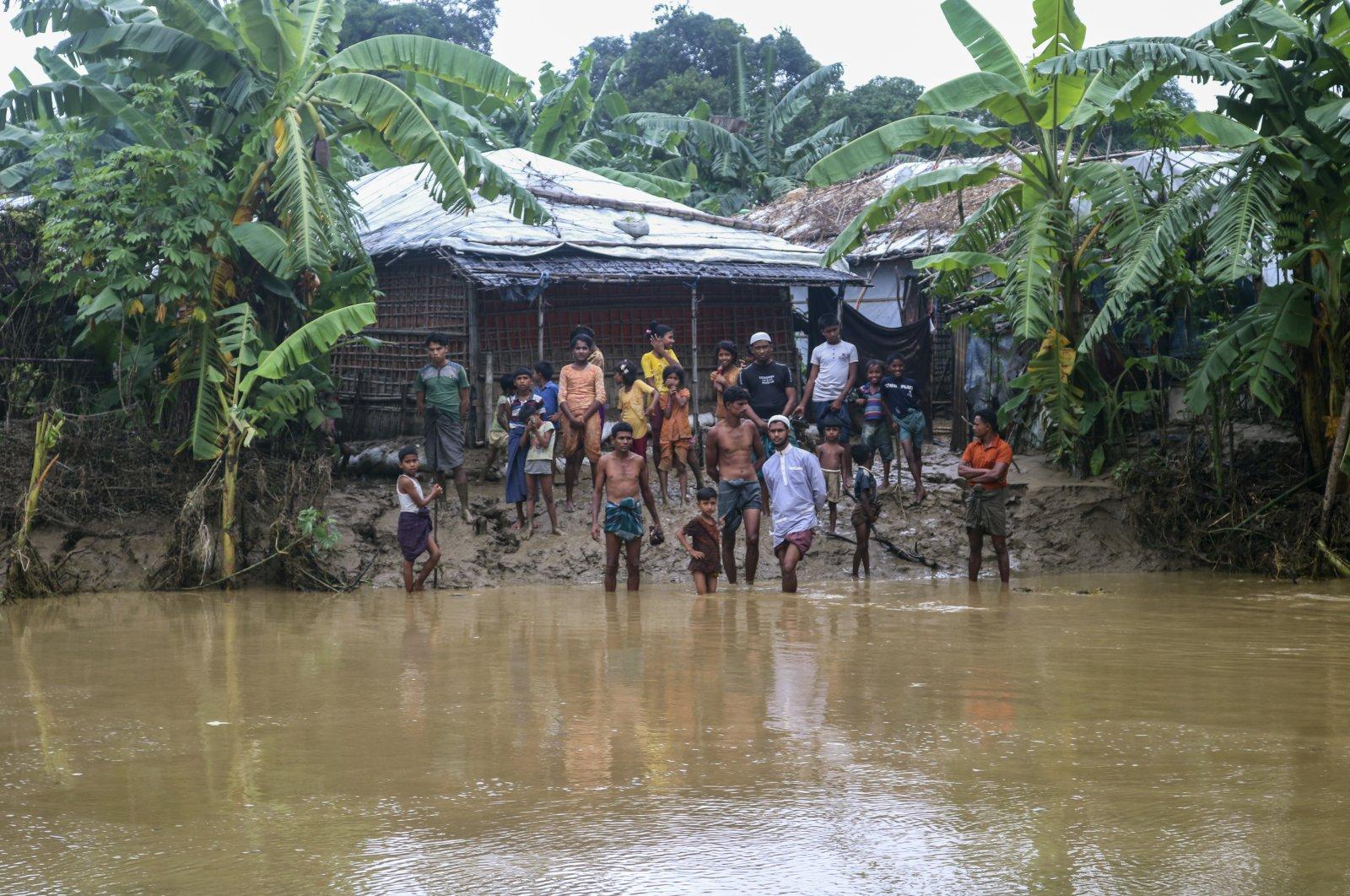 Rohingya refugees look at floodwater following heavy rains at the Rohingya refugee camp in Kutupalong, Bangladesh, July 28, 2021. (AP Photo)