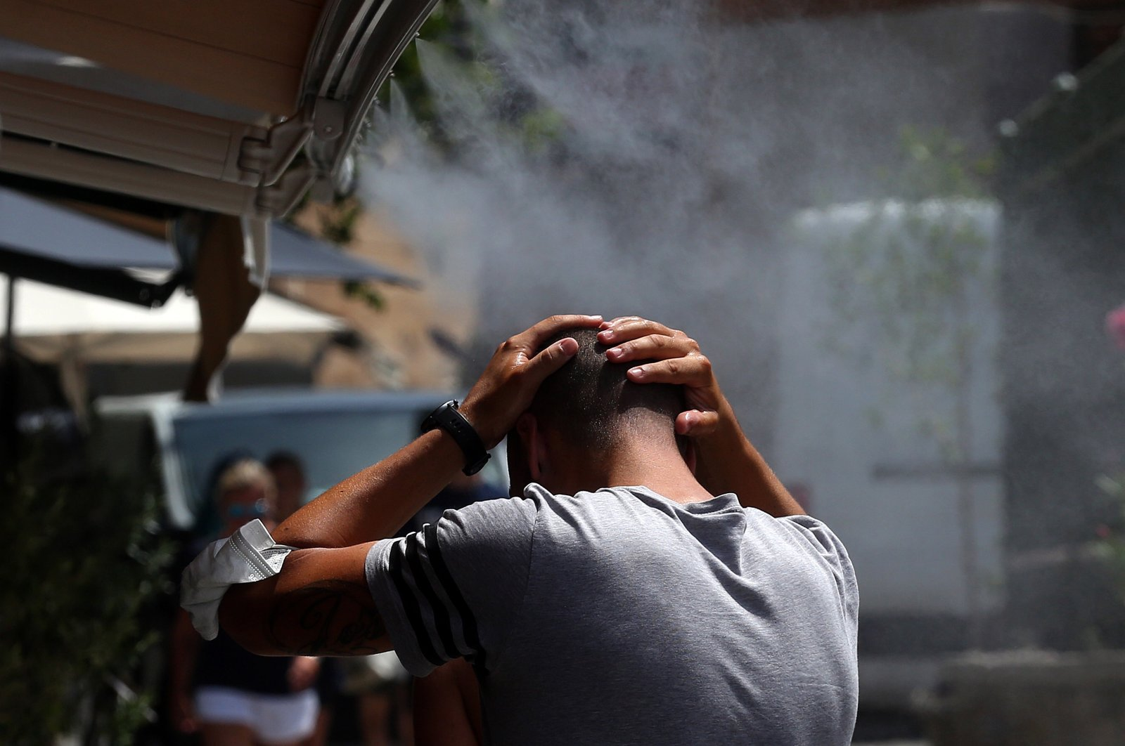 People cool off using a water spray device during a heat wave, in Athens, Greece, Aug. 2, 2021. (EPA Photo)