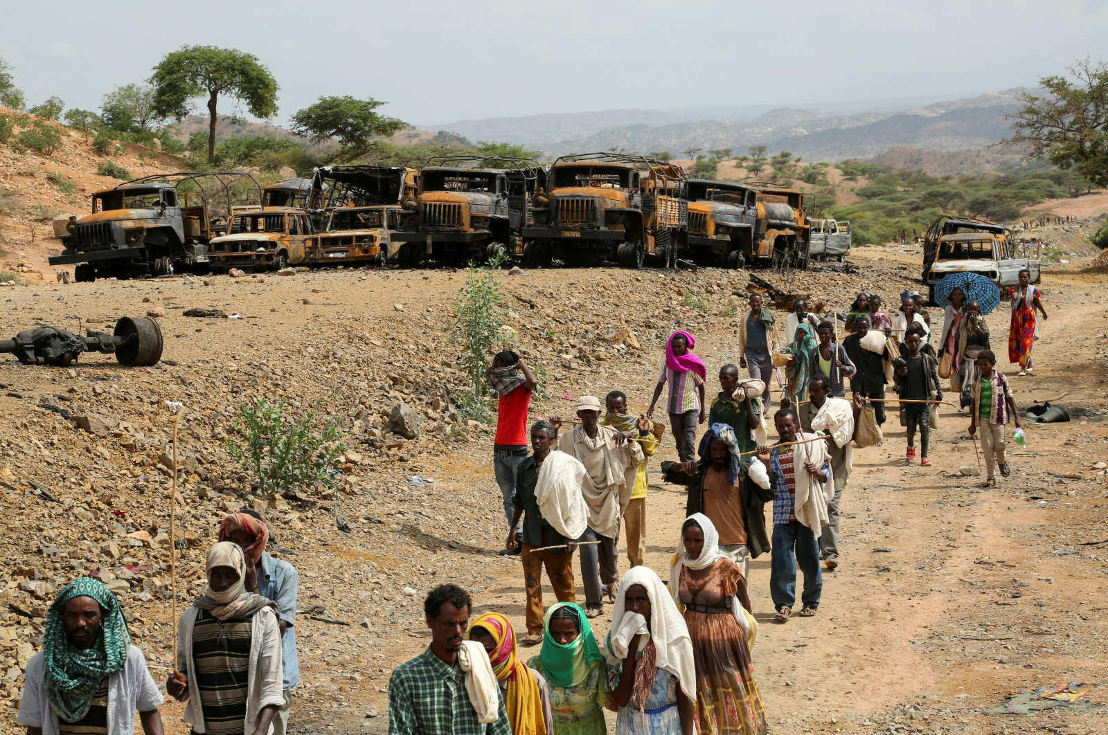 Villagers return from a market to Yechila town in south central Tigray walking past scores of burned vehicles, in Tigray, Ethiopia, July 10, 2021. (Reuters Photo)