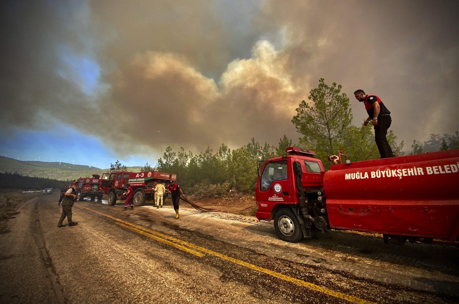 Firefighters work to extinguish an advancing fire, near Bodrum, Muğla, Turkey, Aug. 2, 2021. (AP Photo)